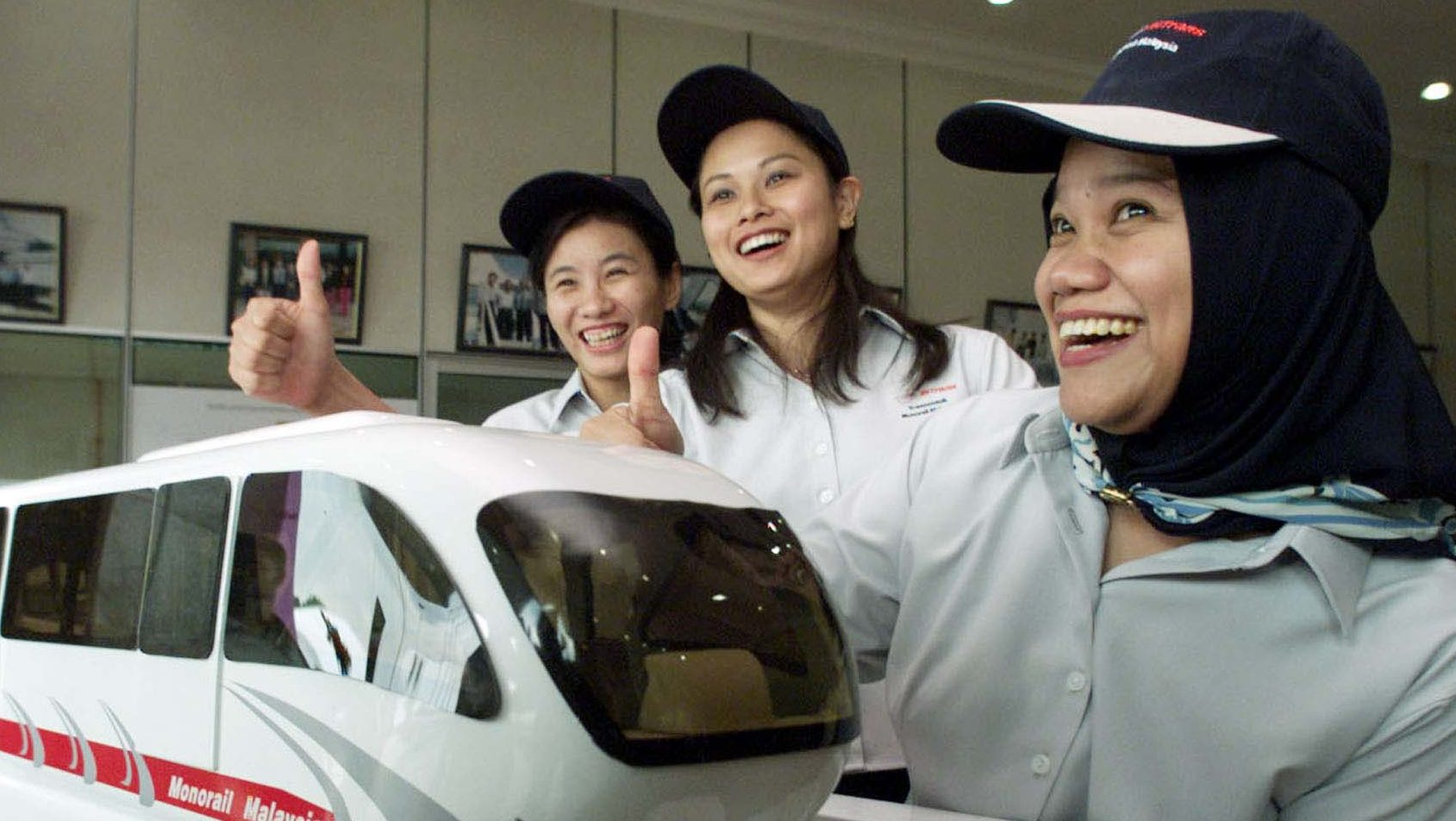Monorail Malaysia Technology staff members (L to R) Ong Pei Fong, Mak Jyhmin and Shamsidar Jazuri give the thumbs up signs next to the first made-in-Malaysia light rail trains model after the launch near Kuala Lumpur May 28, 2001. Monorail Malaysia Technology, a sister company of KL Monorail on Monday will produce 24 cars as well as provide signalling, electrical and power systems for KL Monorail. - PBEAHULATCP