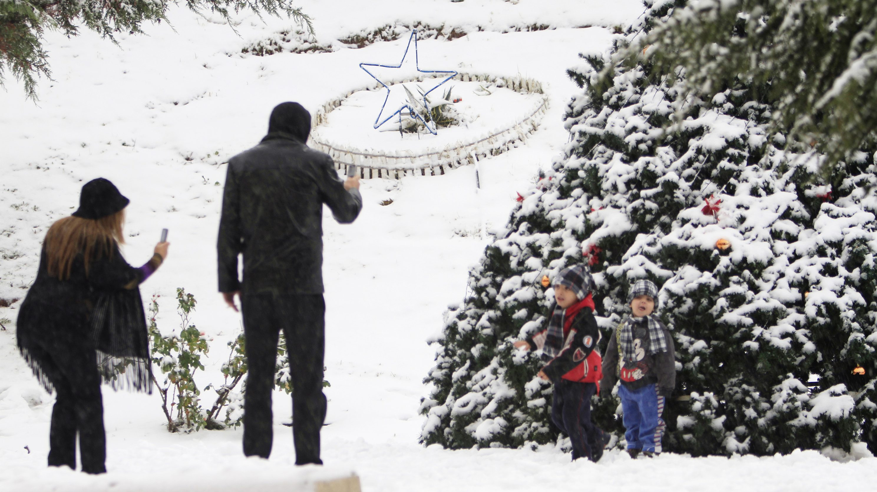 A man and a woman take photos of their children next to a Christmas tree after a snow storm hit Bahamdoun village in eastern Lebanon, December 12, 2010.