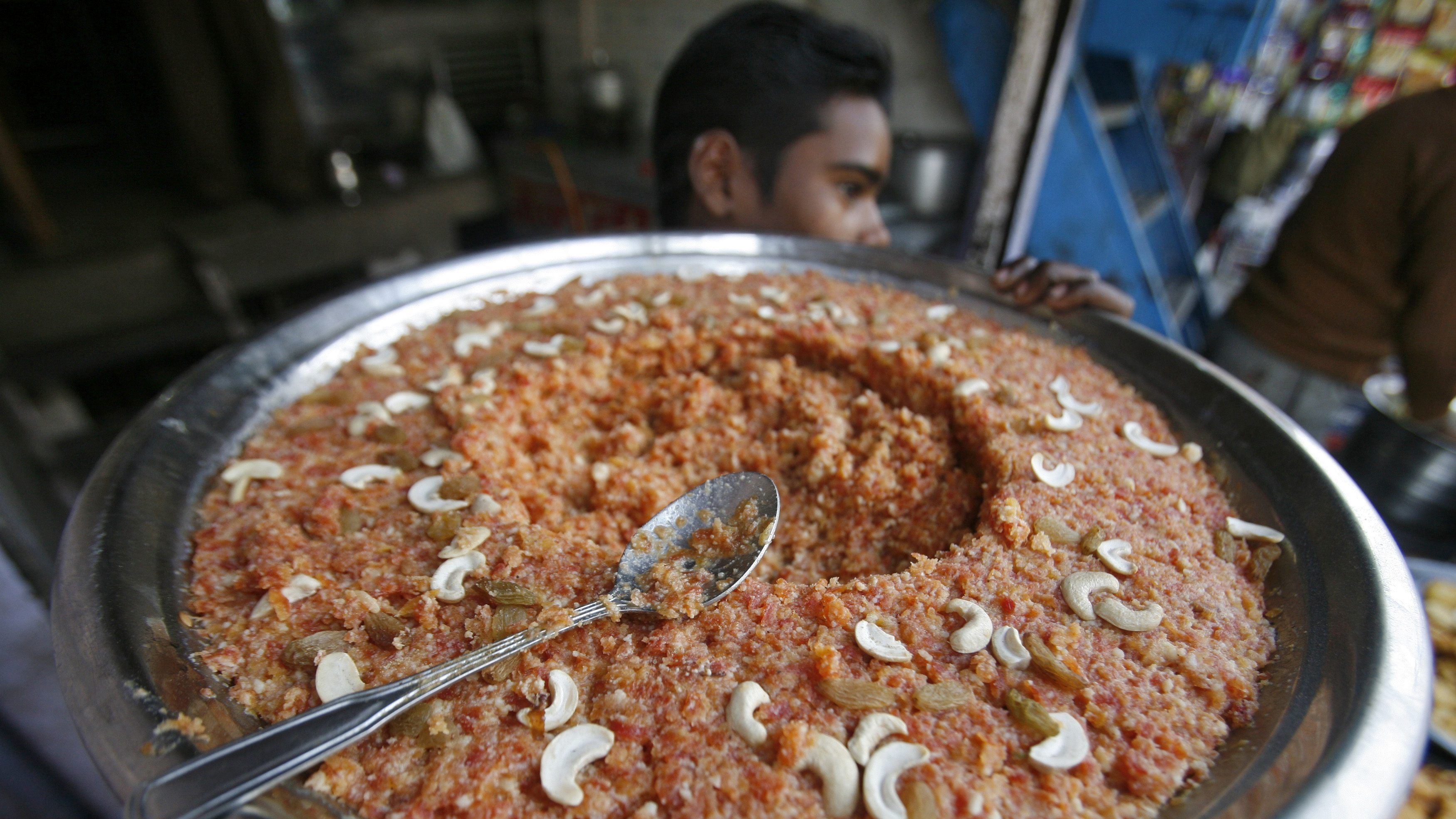 A worker carries gaajar ka halwa, a sweet dish made from carrots and milk, to a shop at Noida in the northern Indian state of Uttar Pradesh, December 23, 2010. India's food price index rose 12.13 percent in the year to December 11, government data on Thursday showed.