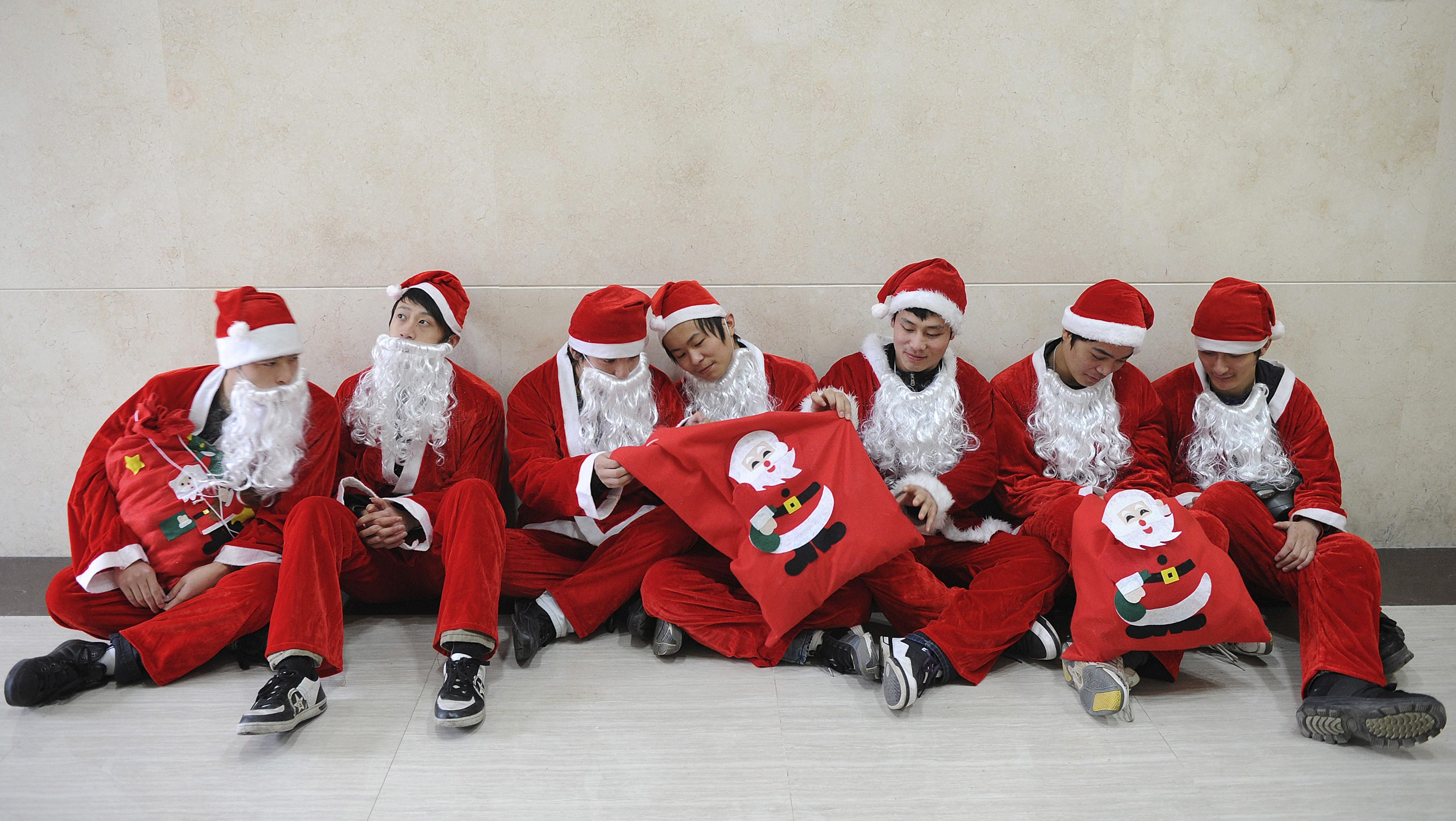 Workers dressed as Santa Claus to celebrate the upcoming Christmas Day, rest at a shopping mall in Hefei, in Anhui province December 24, 2010. REUTERS/Stringer (CHINA - Tags: RELIGION EMPLOYMENT BUSINESS SOCIETY) - GM1E6CO18W001