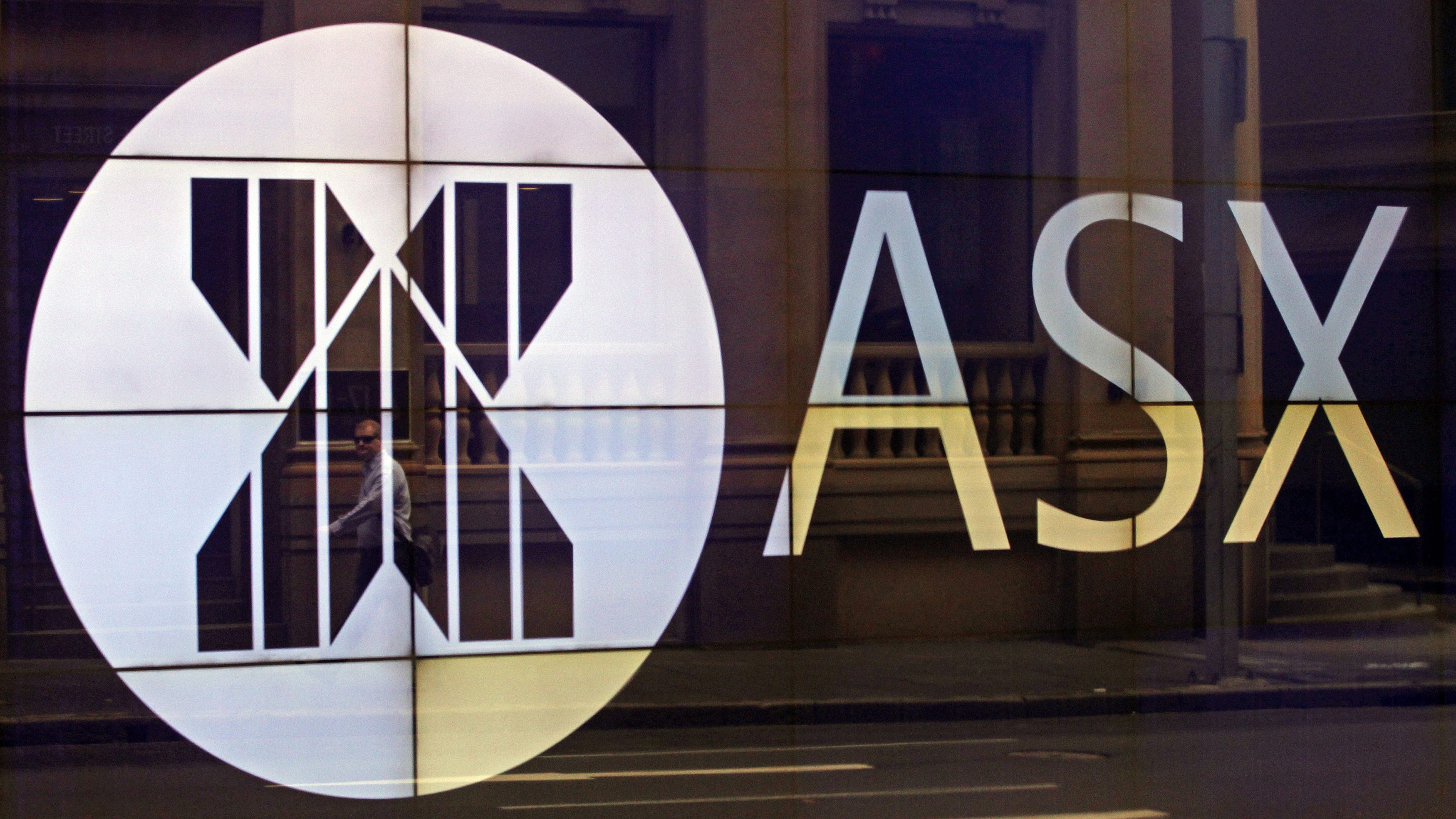 An office worker walks past the board of the Australian Securities Exchange building displaying its logo in central Sydney April 5, 2013. Australian shares inched up 0.1 percent on Friday, supported by the Bank of Japan's aggressive new stimulus policies to jump-start the Japanese economy, news that nudged Wall Street into positive territory overnight. REUTERS/Daniel Munoz (AUSTRALIA - Tags: BUSINESS LOGO) - GM1E9450KXA01