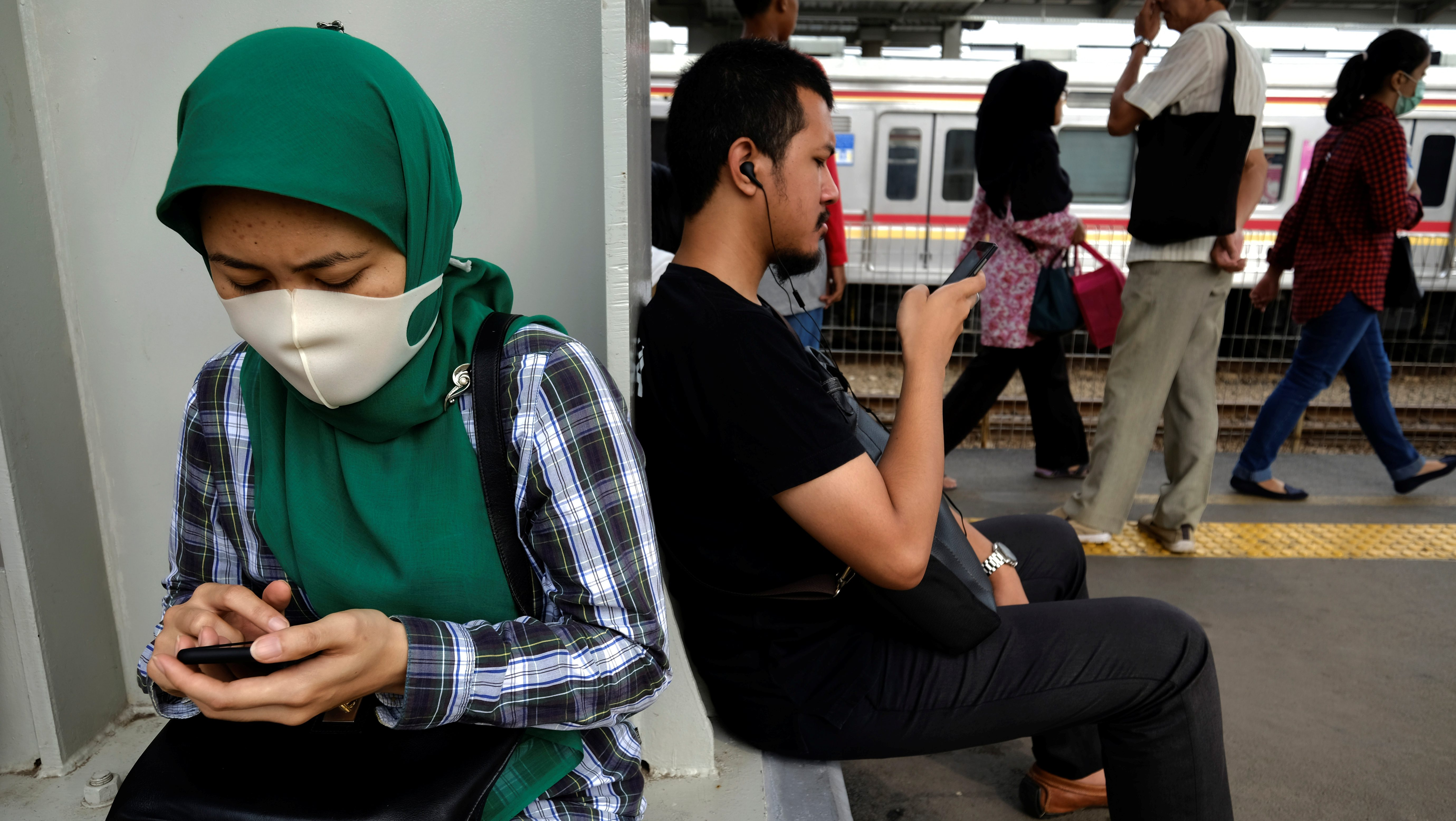 Commuters use their smartphones as they wait for the train during the morning rush at Tanah Abang train station in Jakarta, Indonesia, June 13, 2017.