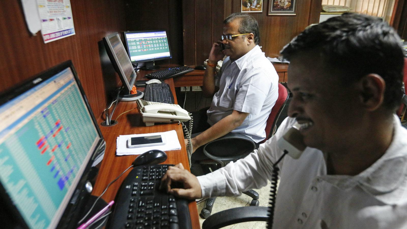 Brokers trade at their computer terminals at a stock brokerage firm in Mumbai