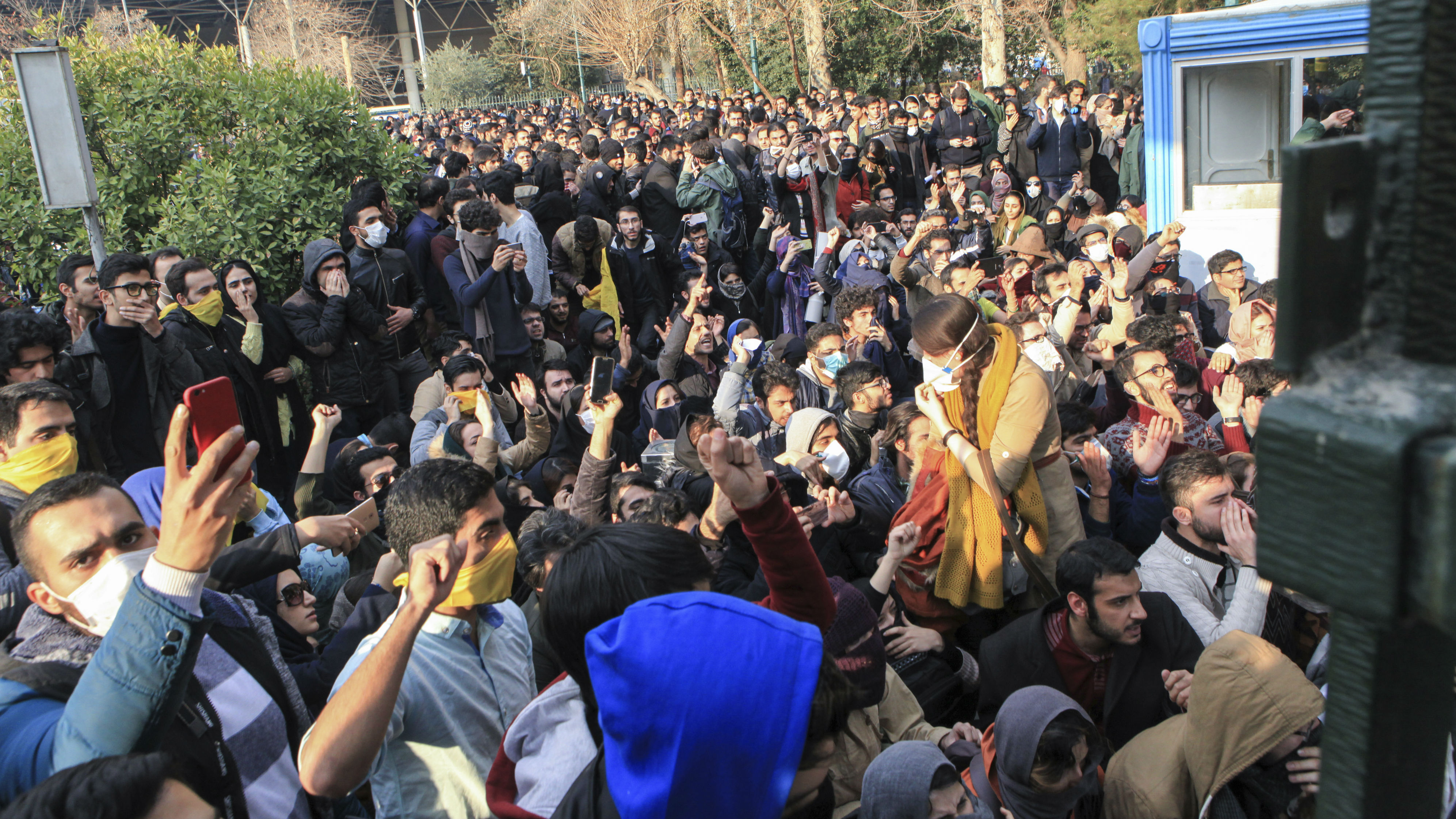 FILE - In this Saturday, Dec. 30, 2017 file photo taken by an individual not employed by the Associated Press and obtained by the AP outside Iran, university students attend a protest inside Tehran University while anti-riot Iranian police prevent them to join other protestors, in Tehran, Iran. As protests over Iran's faltering economy rapidly spread across the country, a channel on a mobile messaging app run by an exiled journalist helped fan the passions of some of those who took to the street. The Telegram app shut down a channel run by Roohallah Zam after Iranian authorities complained that it was inciting violence.