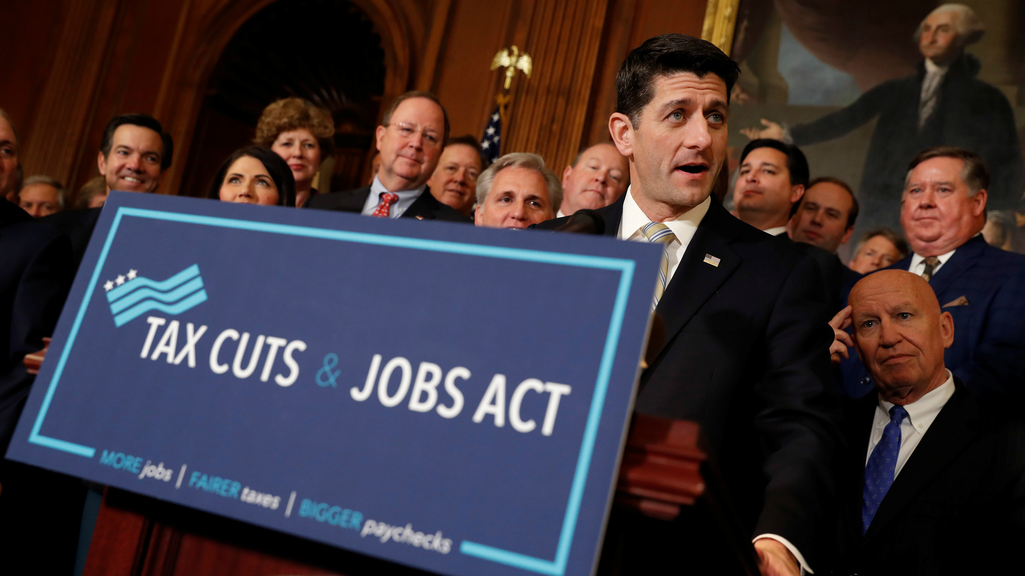 Paul Ryan next to a Tax Cuts and Jobs Act sign.