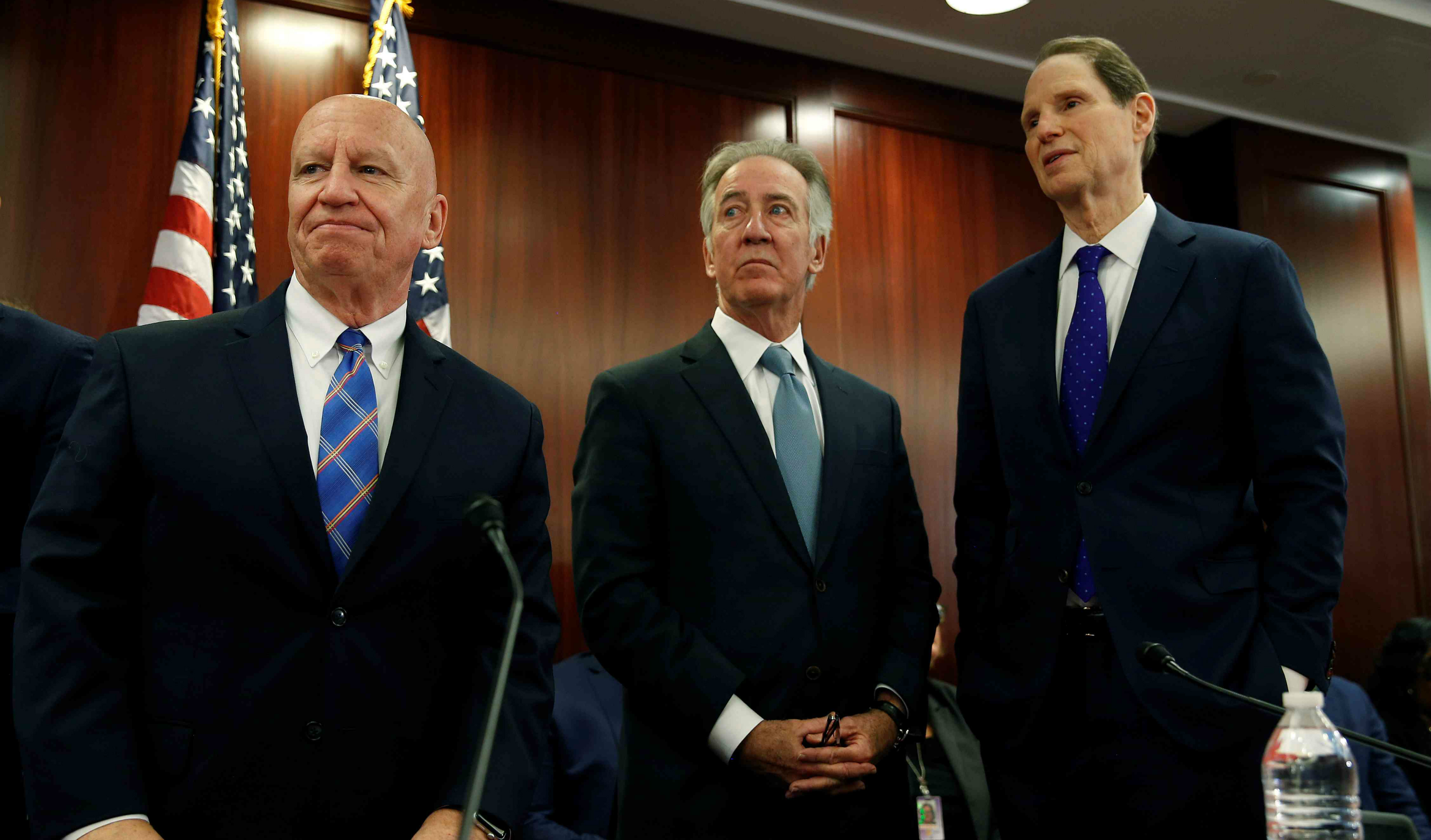 "Chairman of the House Ways and Means Kevin Brady (R-TX), Rep. Richard Neal (D-MA) and Senator Ron Wyden stand before the House-Senate Conferees hold an open conference meeting on the ""Tax Cuts and Jobs Act"" on Capitol Hill in Washington, U.S., December 13, 2017."