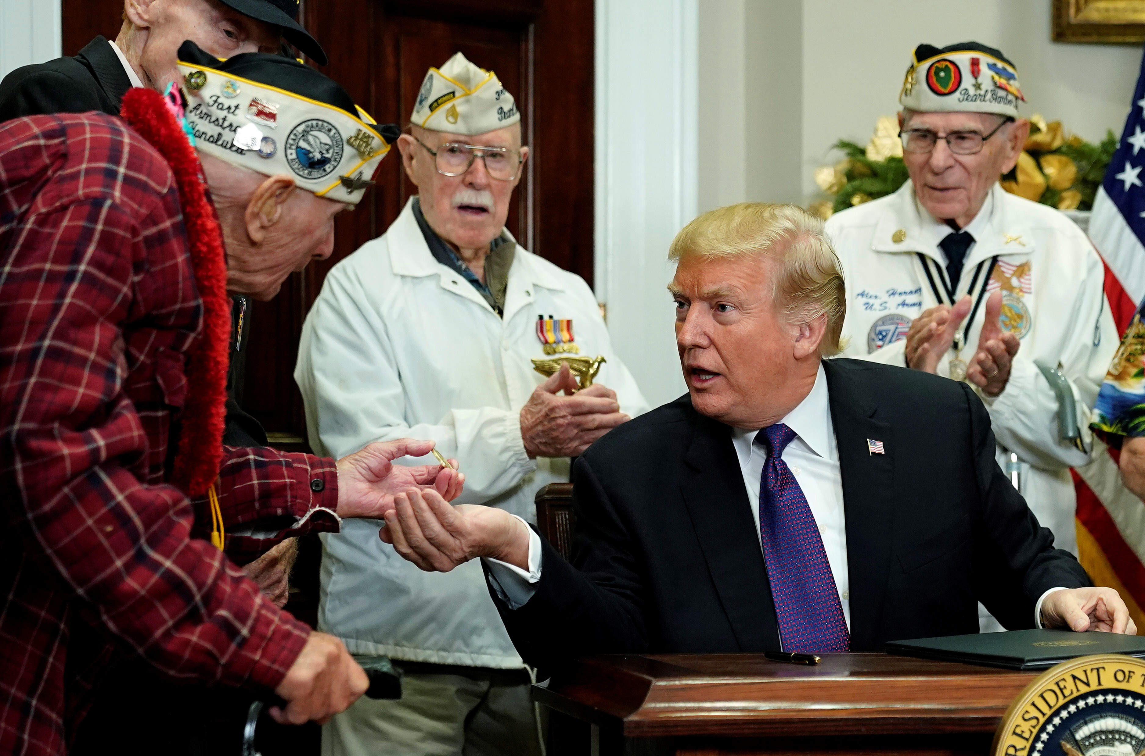 Veteran showing Trump a coin.
