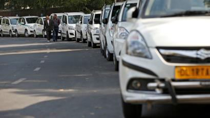 Drivers of Uber and Ola walk next to their parked vehicle's during a protest in New Delhi