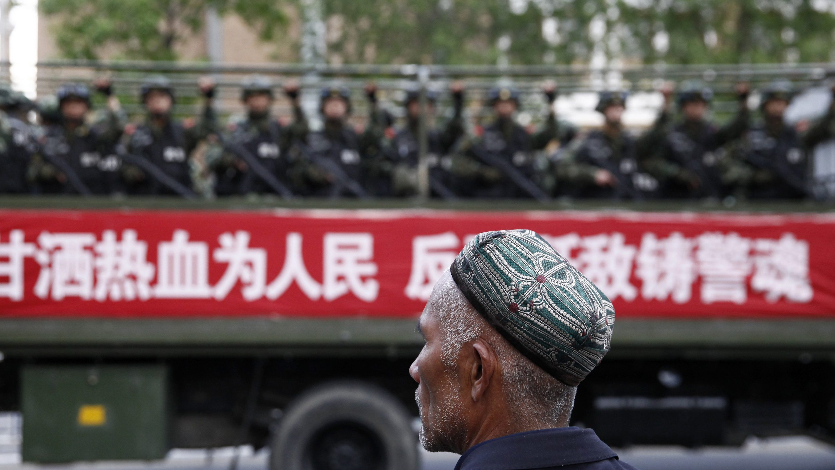 """A Uighur man looks on as a truck carrying paramilitary policemen travel along a street during an anti-terrorism oath-taking rally in Urumqi, Xinjiang Uighur Autonomous Region May 23, 2014. China launched a one-year campaign against terrorist violence in Xinjiang Uighur Autonomous Region on Friday, after 39 people were killed and 94 injured in a terrorist attack on Thursday, Xinhua News Agency reported. The Chinese characters on the banner read, """"Willingness to spill blood for the people. Countering terrorism and fighting the enemies is part of the police spirit."""" Picture taken May 23, 2014. REUTERS/Stringer"""