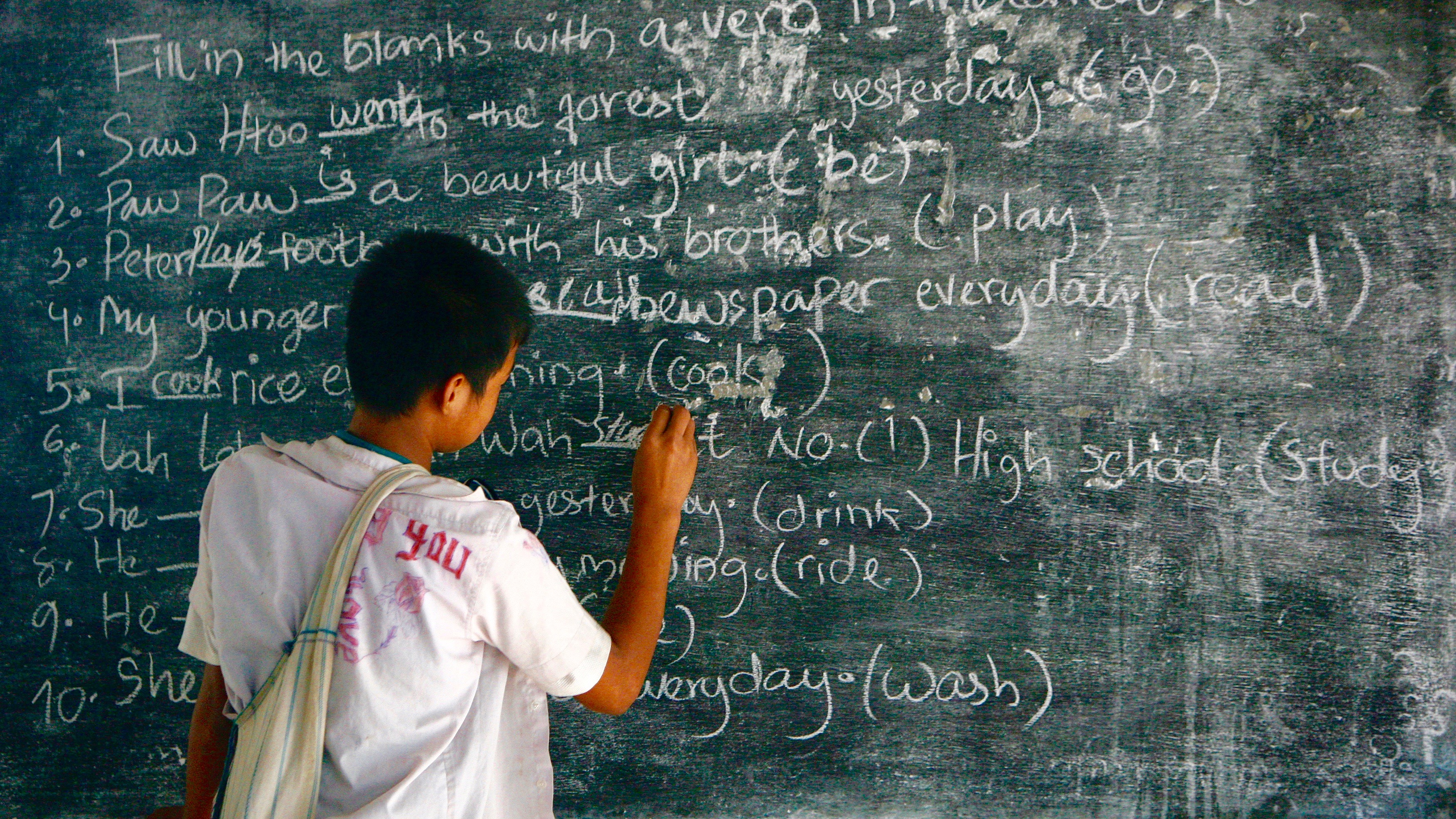 Boy at chalkboard writing in English (Thailand).