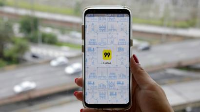 A photo illustration shows the 99 app on a mobile telephone, as it is held up for a posed photograph