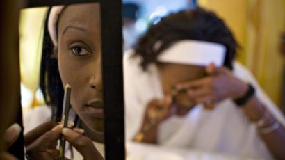 A contestant hoping to become a supermodel is reflected in a mirror while applying make-up during a competition in Kenya's capital Nairobi August 25, 2008. New York's Ford modelling agency scoured remote areas of Kenya hoping to find a potential supermodel and on Thursday selected 15 finalists, including one rural contestant who had never before worn high heels.