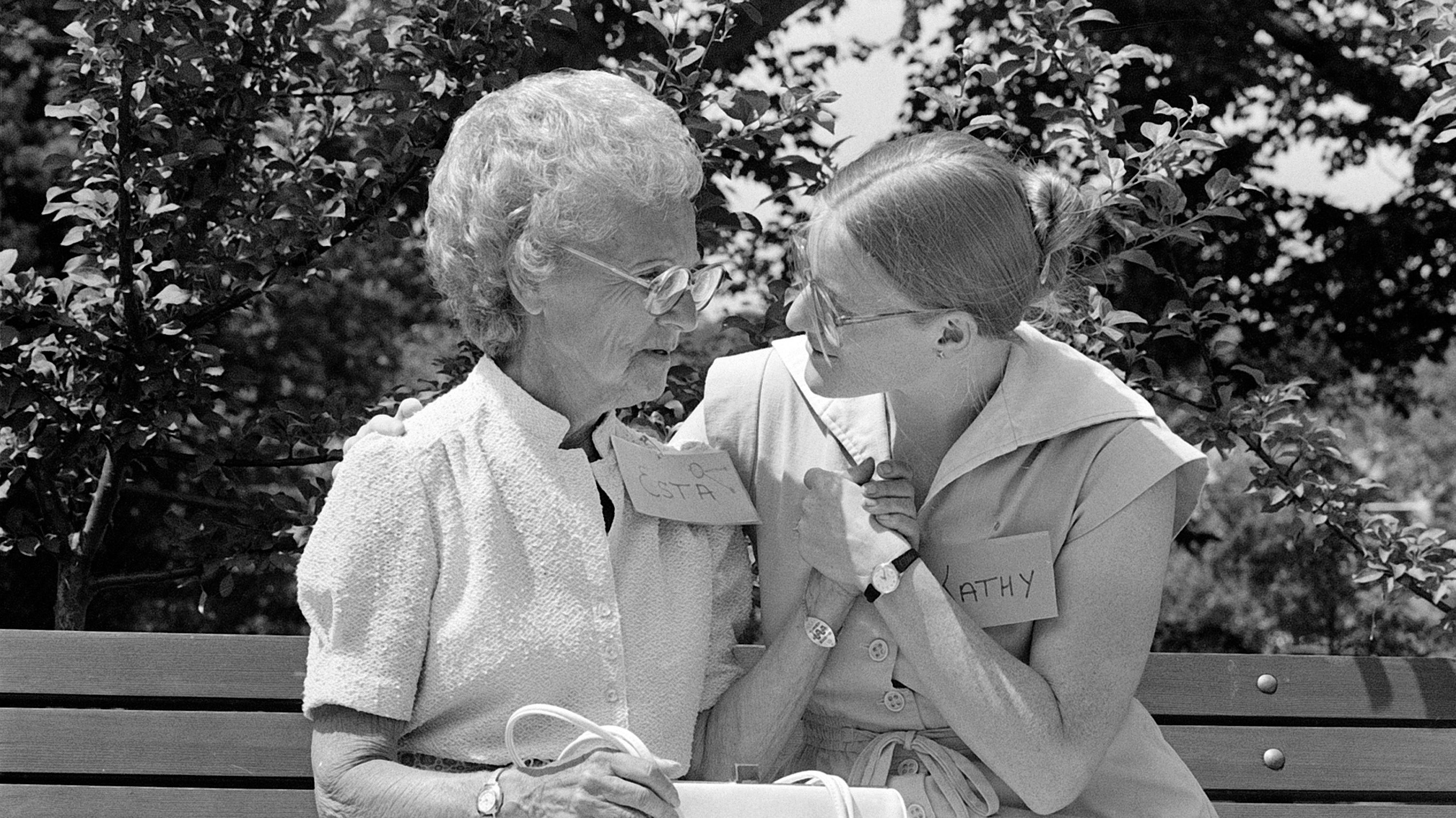 Kathy Thoen, right, a social worker at the Community Family Adult Day Health Center in Medford, Mass., holds hands with a woman identified as Esta, left, who has Alzheimer's disease, at the opening of the center's Alzheimer's program, June 19, 1984.