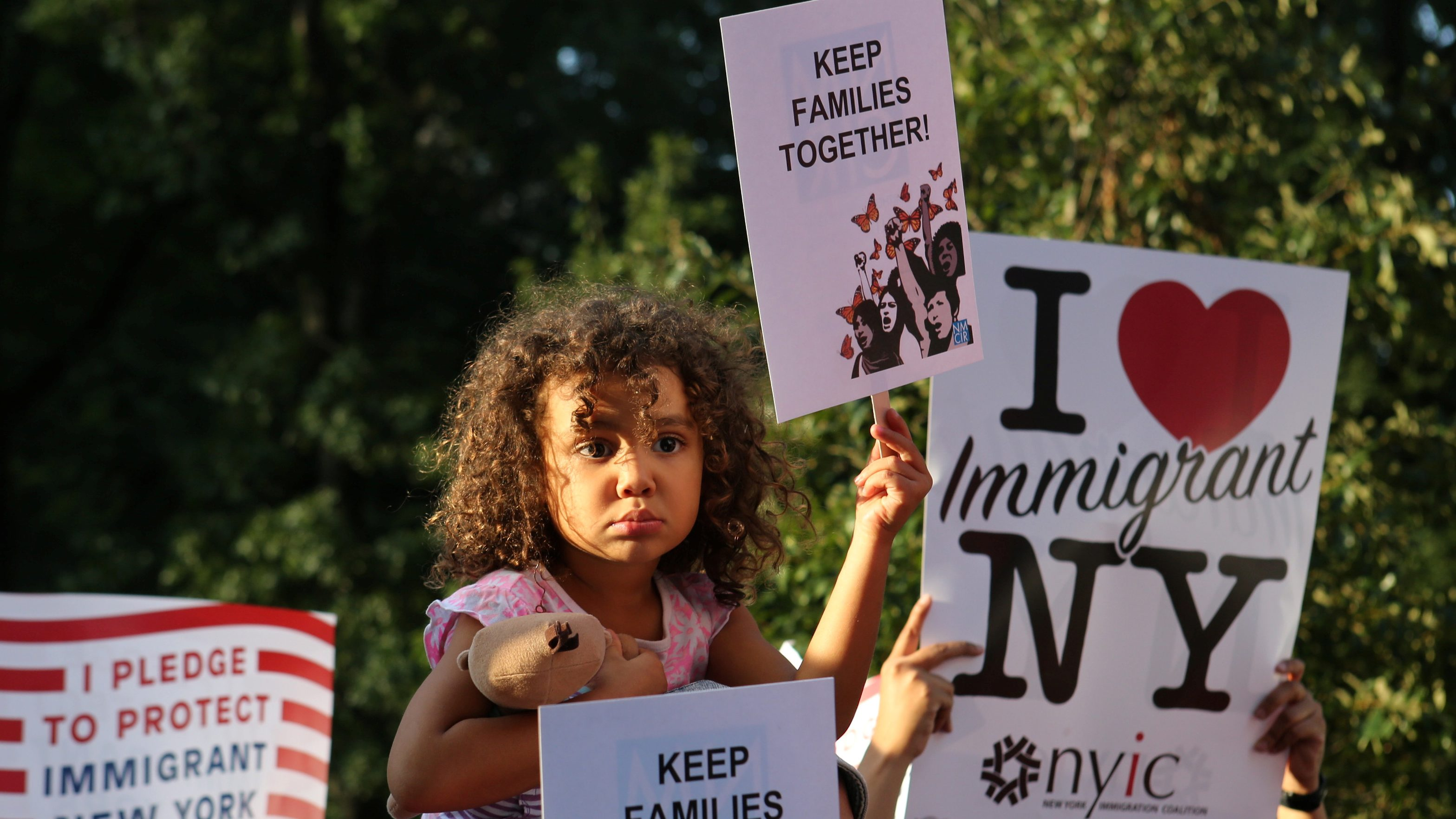 """A girl sitting on the shoulders of her father holds a sign reading """"Keep Families Together"""""""