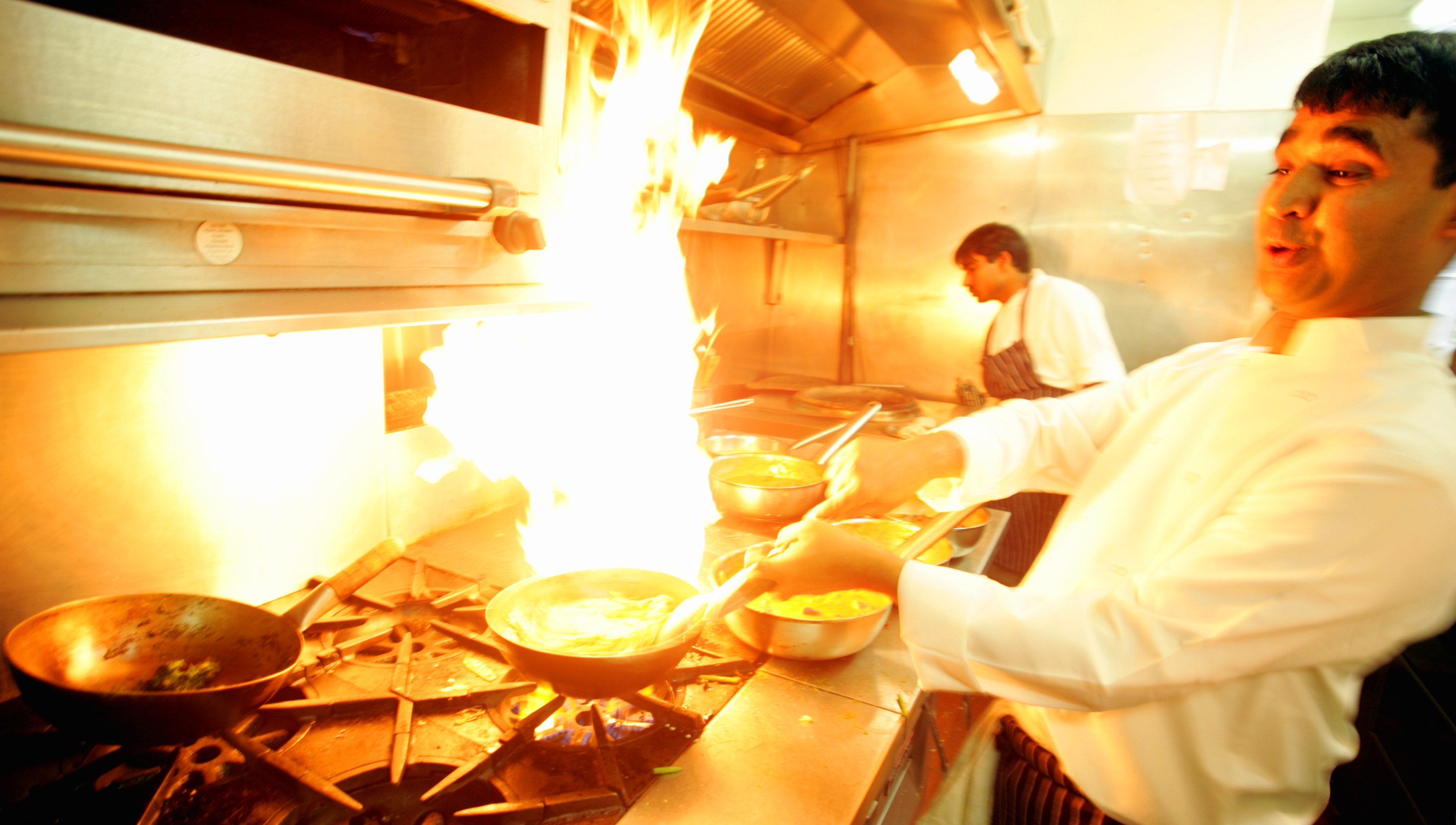 A chef in in the Deyna restaurant stands back as he cooks a hot Indian dish, in London, Thursday Sept 29, 2005, as a plaque dedicated to Sake Dean Mahomed is unveiled nearby, at the site of Britain's first curry house. The original curry house founded in 1810 and advertised Indian dishes of highest perfection, which started the British love affair with curry, now as popular at fish and chips. India-born Sake Dean Mahomed was a shampooist for King George IV and a soldier with the East India Company's army, but it was the curry house that he started in 1810 that brought him fame. (AP Photo/Alastair Grant)