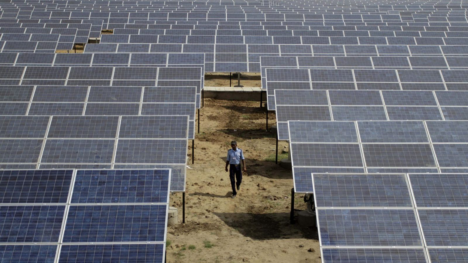 An Indian security guard walks among solar panels at the newly inaugurated solar photovoltaic power plant at Khadoda, in Sabarkantha district, about 90 kilometers (56 miles) from Ahmadabad, India, Friday, June 10, 2011. Gujarat chief Minister Narendra Modi unveiled the power plant of Azure Power, one of the largest utility-scale solar power plants in the country. (AP Photo/Ajit Solanki)