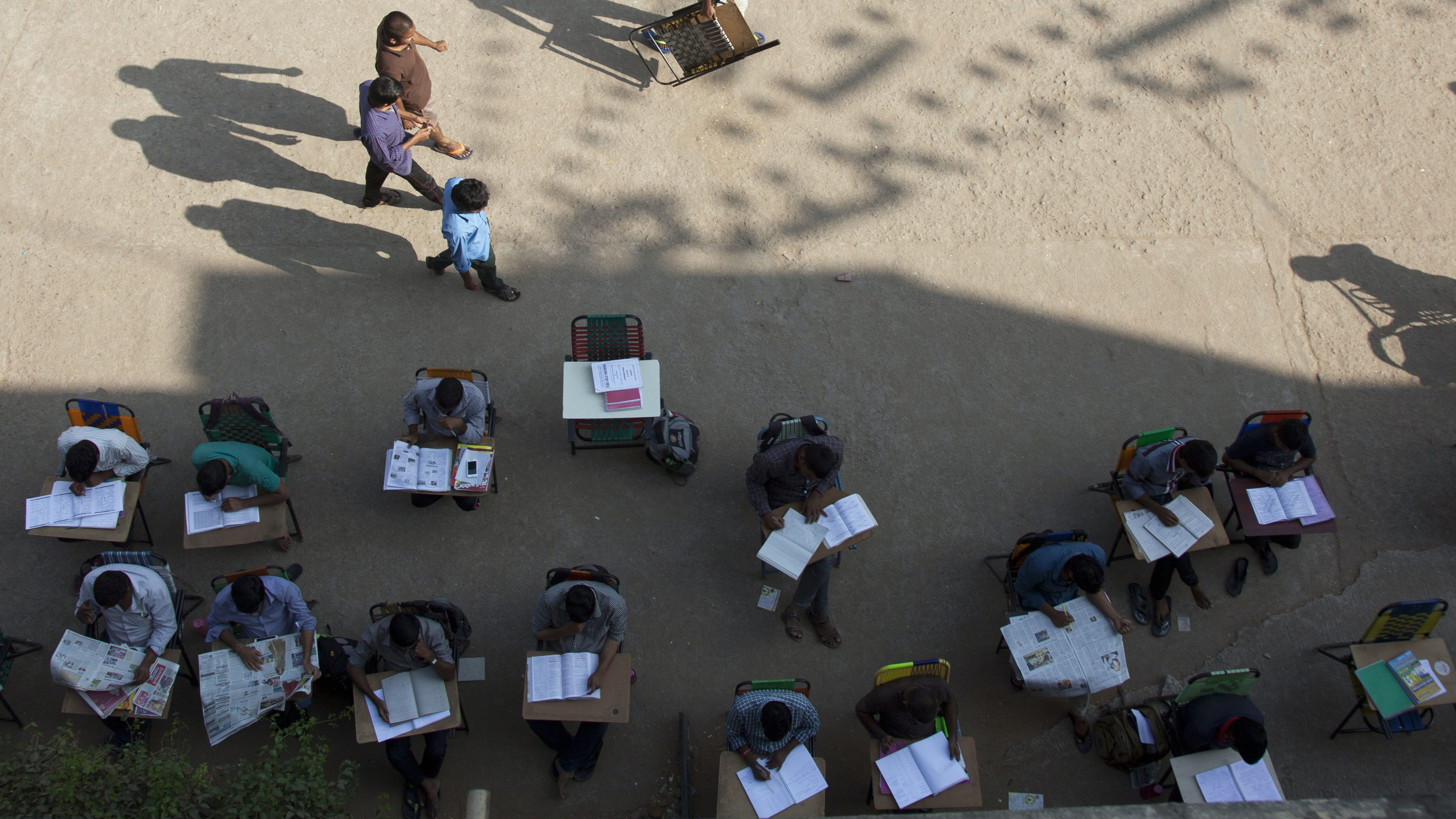 In this Friday, Feb. 17, 2017 photo, a man arrives holding a chair to join other college students and job-seekers study in an open ground outside the City Central Library in Hyderabad, India. Hundreds of young college students and job-seekers, armed with their books and other study material sit and prepare for examinations till late at night in the vicinity of this library. Many of them bring their own chairs, which they chain to the outer metal grill of the building overnight. High levels of unemployment, even among the educated, creates immense pressure on young people to find work, and more so for a secure government job. Nowhere is the search for jobs more desperate than in India where around 13 million young people enter the job market every year. (AP Photo/Mahesh Kumar A.)