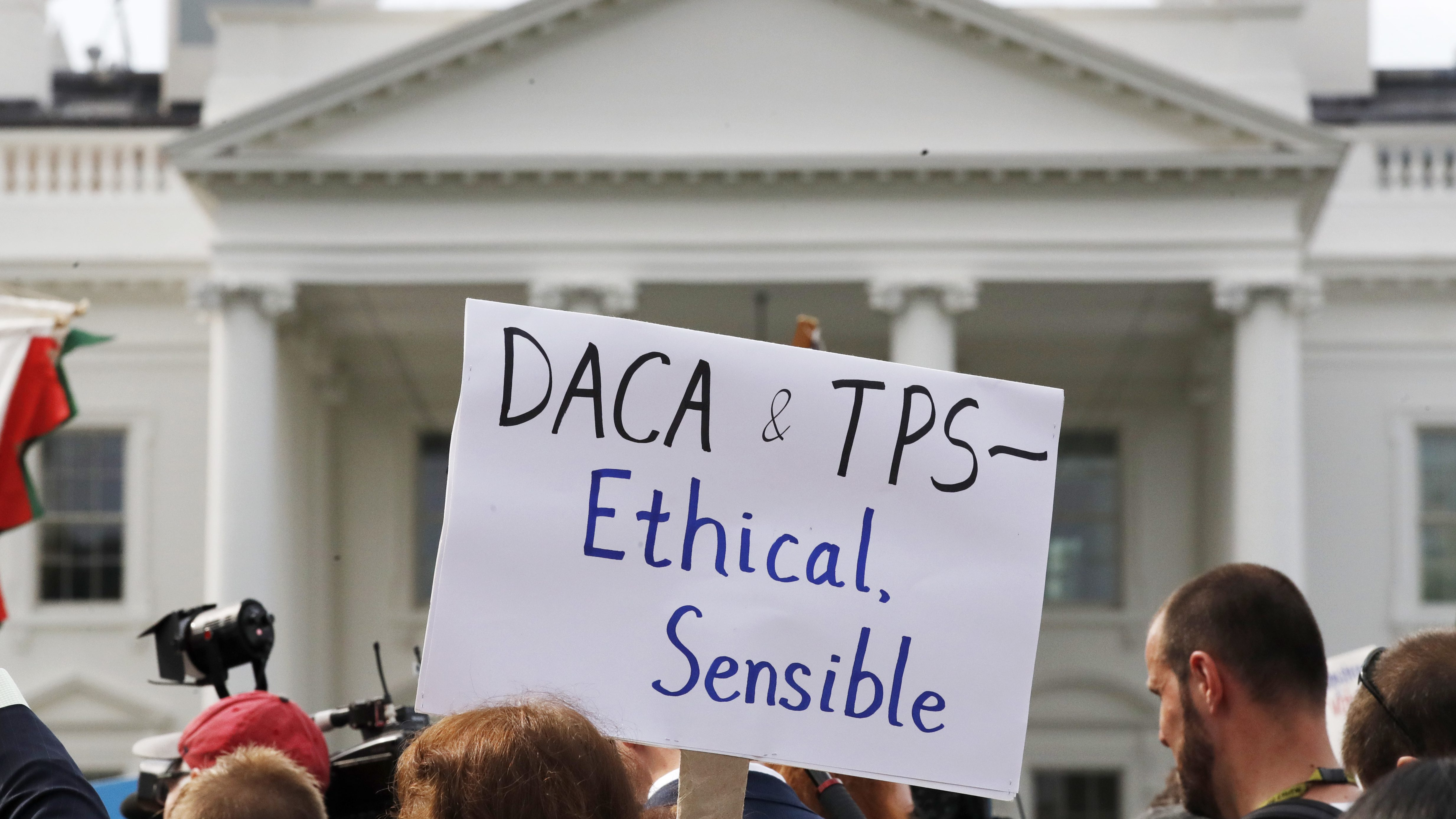 """A person holds up a sign in support of the Deferred Action for Childhood Arrivals, known as DACA, and Temporary Protected Status programs during a rally in support of DACA and TPS outside of the White House, in Washington, Tuesday, Sept. 5, 2017. President Donald Trump's administration will """"wind down"""" a program protecting hundreds of thousands of young immigrants who were brought into the country illegally as children, Attorney General Jeff Sessions declared Tuesday, calling the Obama administration's program """"an unconstitutional exercise of authority.""""  (AP Photo/Jacquelyn Martin)"""