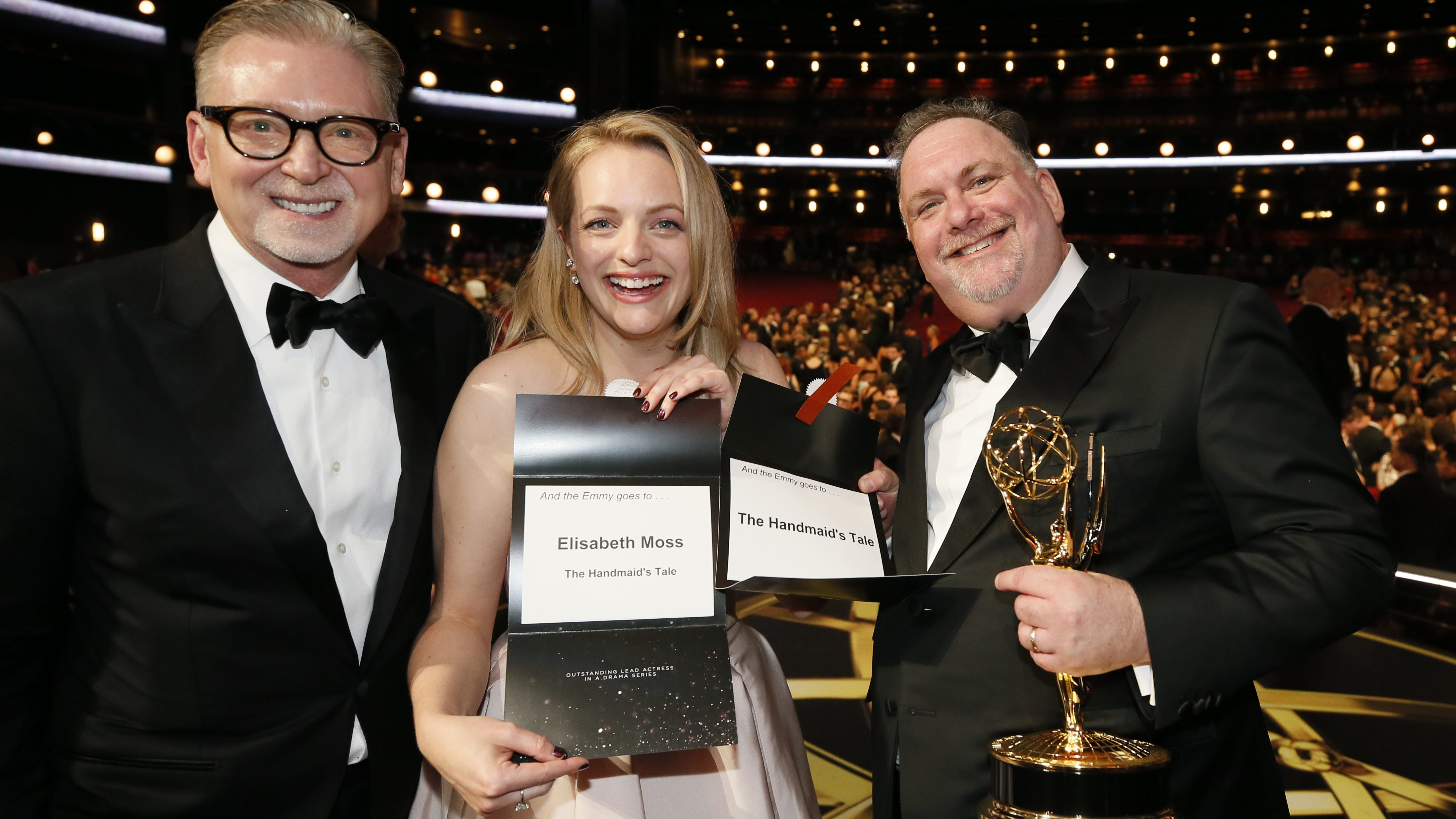 """Warren Littlefield, from left, winner of the award for outstanding drama series for """"The Handmaid's Tale"""", from left, Elizabeth Moss, winner of the award for outstanding lead actress in a drama series for """"The Handmaid's Tale"""" and Bruce Miller, winner award for outstanding drama series for """"The Handmaid's Tale"""" pose on the red carpet stage at the 69th Primetime Emmy Awards on Sunday, Sept. 17, 2017, at the Microsoft Theater in Los Angeles. (Photo by Danny Moloshok/Invision for the Television Academy/AP Images)"""