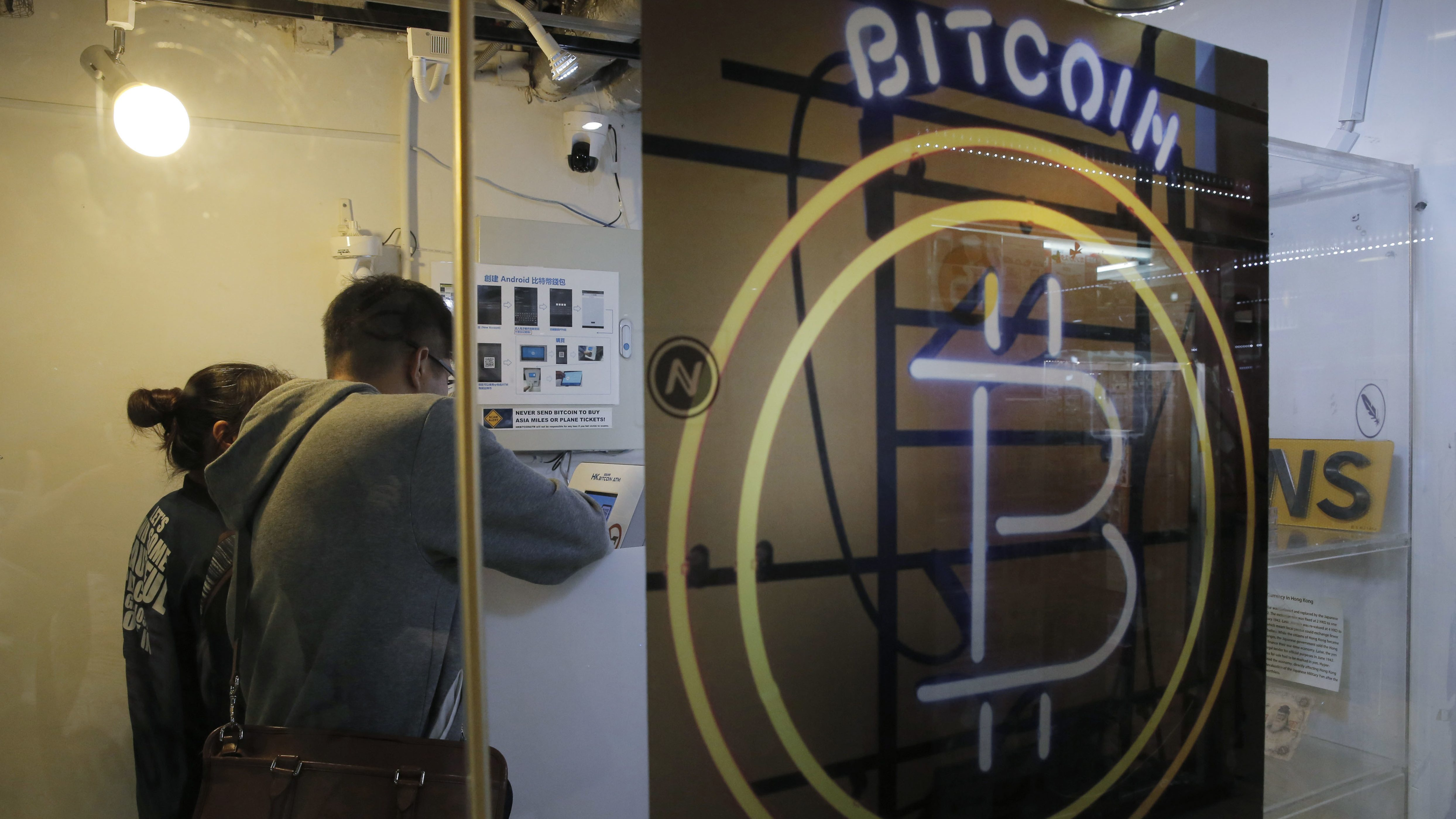 In this Friday, Dec. 8, 2017, photo, people use the Bitcoin ATM in Hong Kong. The launch of a U.S. futures contract for bitcoin on Sunday, Dec. 10, 2017, underscores the virtual currency's increasing mainstream acceptance, including in many parts of Asia, where it already has a wide following among speculators and investors.