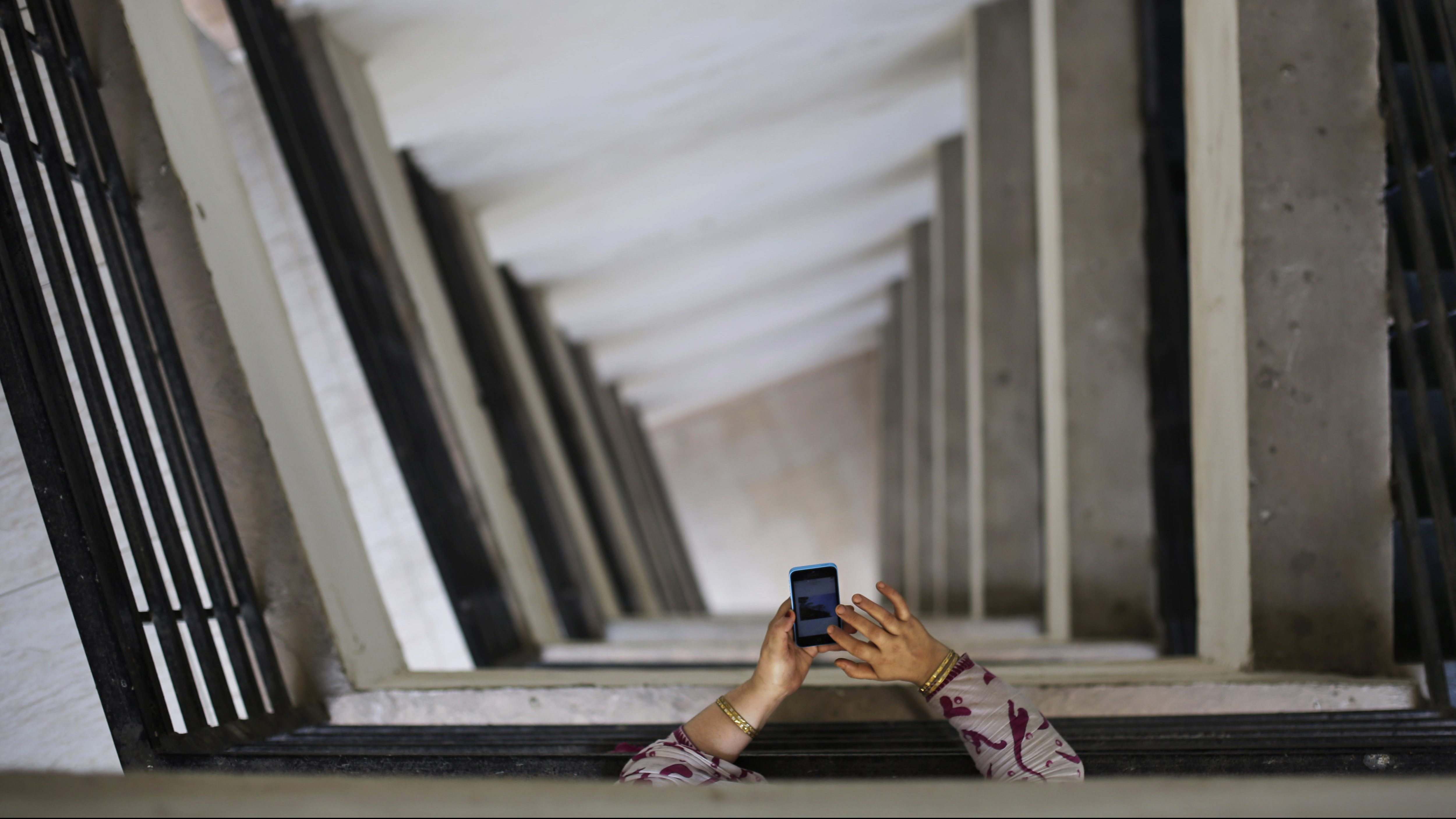 "An Indian woman leans on metal railings as she surfs the internet on her smartphone at a hospital in New Delhi, India, Tuesday, March 24, 2015. India's top court reaffirmed people's right to free speech in cyberspace Tuesday by striking down a provision that had called for imprisoning people who send ""offensive"" messages by computer or mobile phone. The provision, known as Section 66A of the 2008 Information Technology Act, says sending such messages is a crime punishable by up to three years in prison. (AP Photo/Altaf Qadri)"