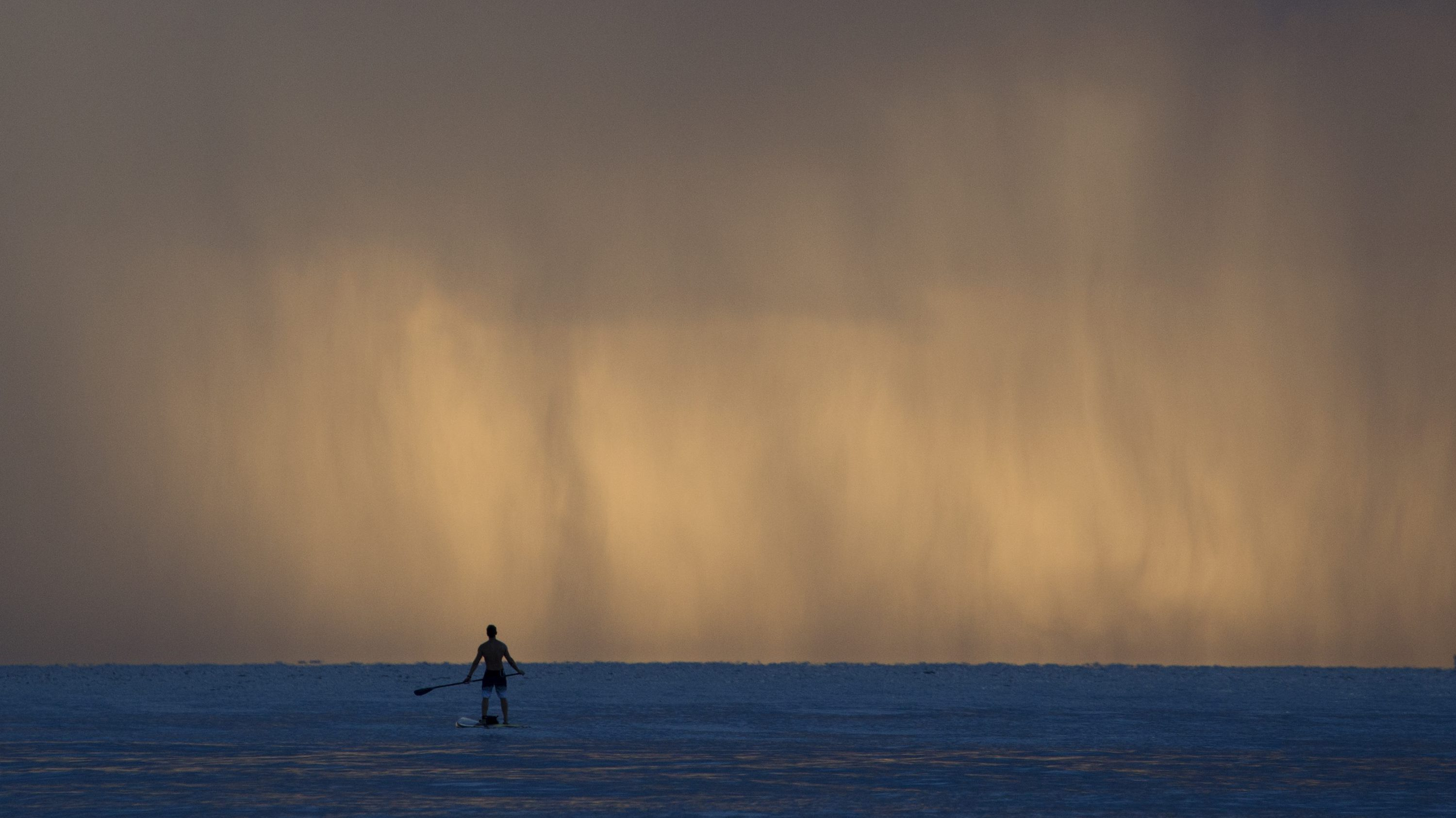 AP10ThingsToSee - Pablo Dona, of Miami pauses while paddleboarding as sheets of rain fall in front of him off the shores of Bal Harbour, Fla., on Tuesday, Sept. 22, 2015.