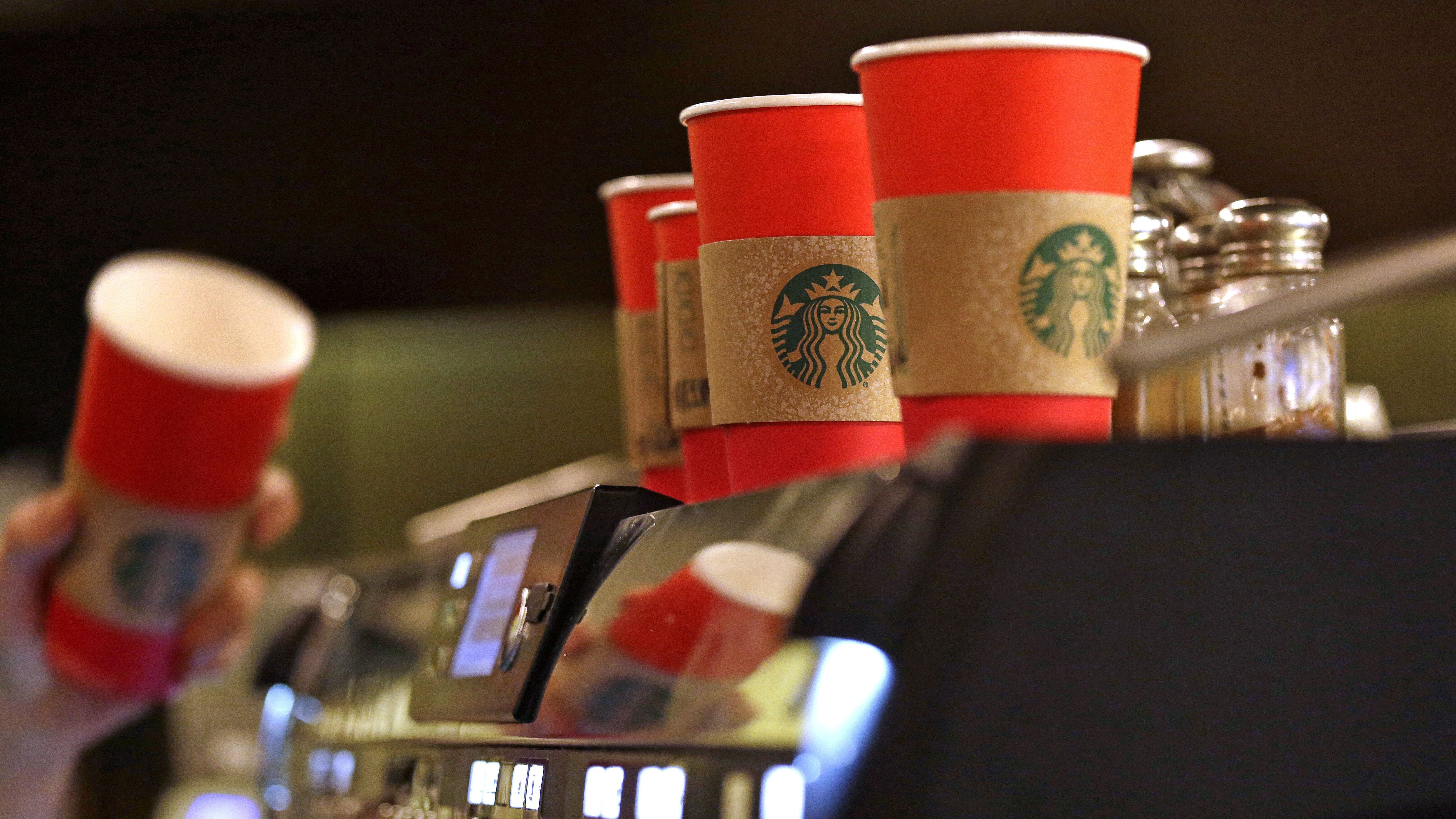 A barista reaches for a red paper cup as more, with cardboard liners already attached, line the top of an espresso machine at a Starbucks coffee shop in the Pike Place Market, Tuesday, Nov. 10, 2015,