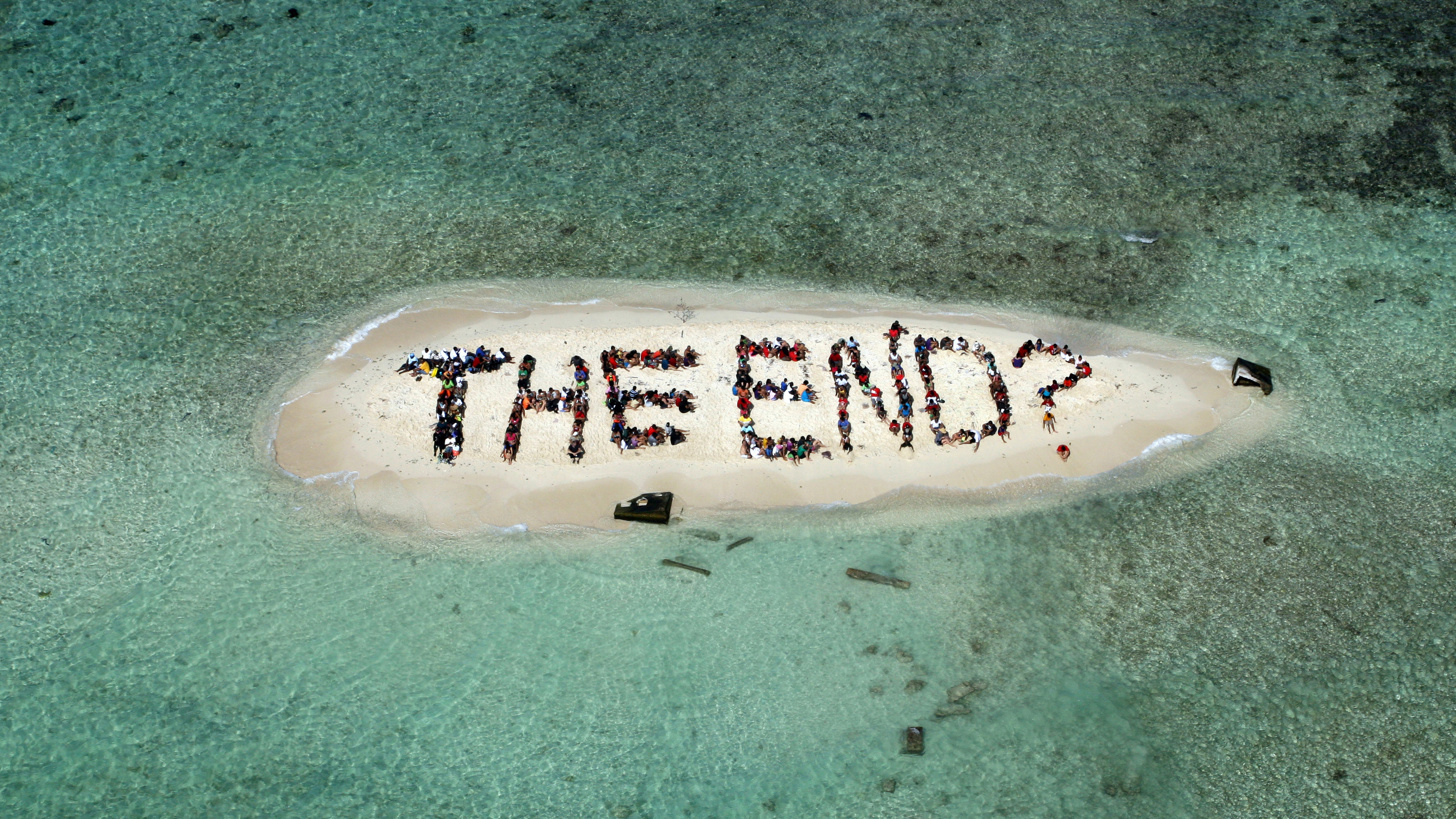 """Hundreds of Belizians and international supporters gather on an island to form a message on the Barrier Reef off the coast of Belize City November 13, 2010. The message, which was to call on humanity to be in harmony with the natural world, was created on the final day of the three-day Belize Reef Summit and is part of the launch of the Harmony Initiative, a partnership between the film """"Harmony"""" narrated by Britain's Prince Charles and the Global Campaign for Climate Action. REUTERS/Lou Dematteis/Spectral Q/Handout"""