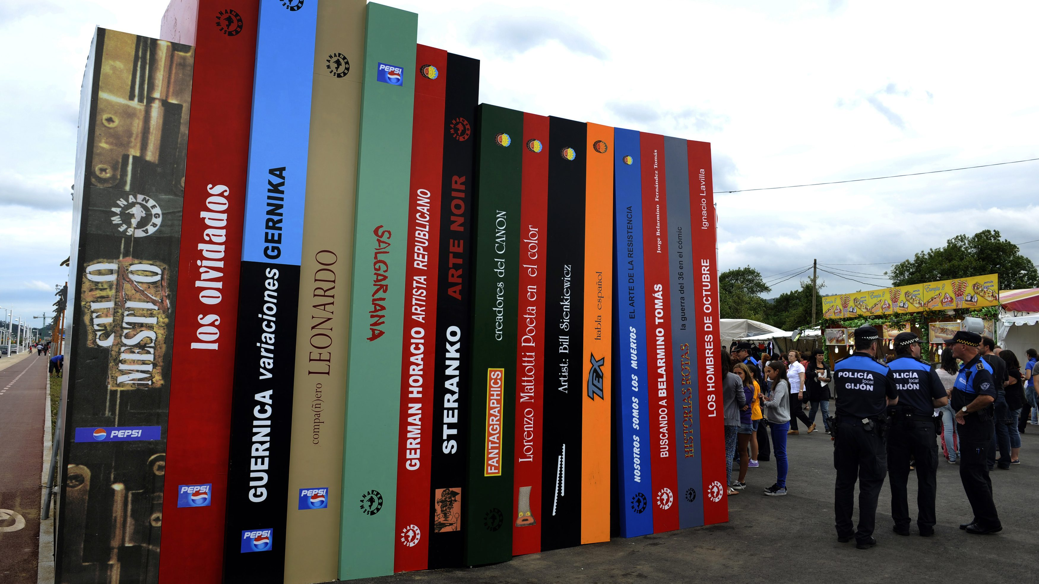 """Big cardboard books welcome visitors at the entrance of the XXIV Semana Negra (Noir Week) book fair in the northern Spanish town of Gijon July 25, 2011. One of Europe's biggest literary festivals convenes for the 24th time in Spain until next July 31st in its annual bid to convince all comers that books are fun by mixing literary events with a fun fair. A million people a year visit ferris wheels and merry-go-rounds at the week-long """"Semana Negra"""", but they also buy 50,000 books and rub shoulders with scores of writers from Europe, Latin America and North America. As well as readings and book launches, the Semana Negra also stages concerts, a photo-journalism exhibition and awards prizes for poetry, crime writing, science fiction, reporting, historical and fantasy novels."""
