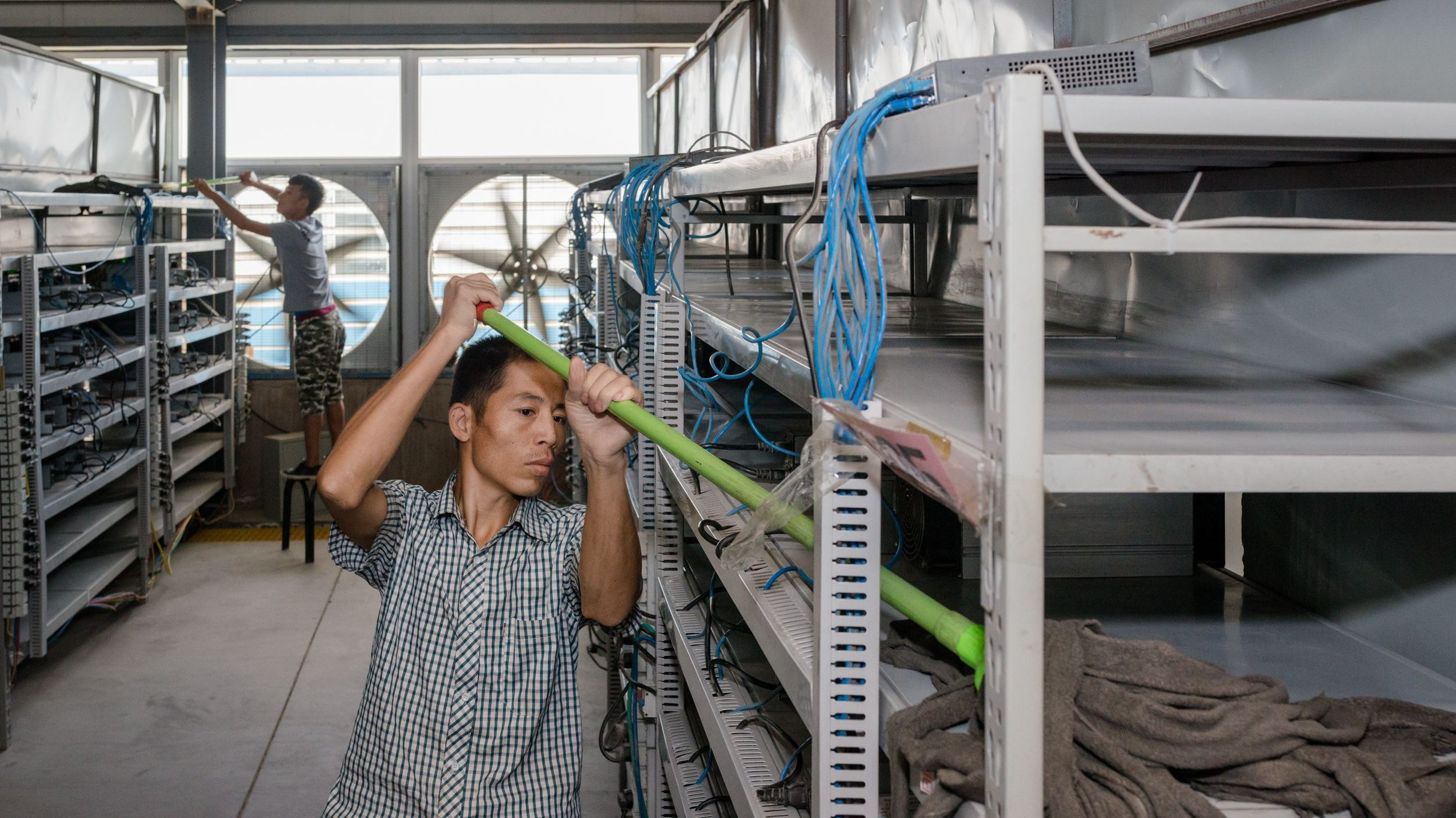 Workers clean the shelves of bitcoin-mining machines in Bitmain's mining operation in Inner Mongolia.