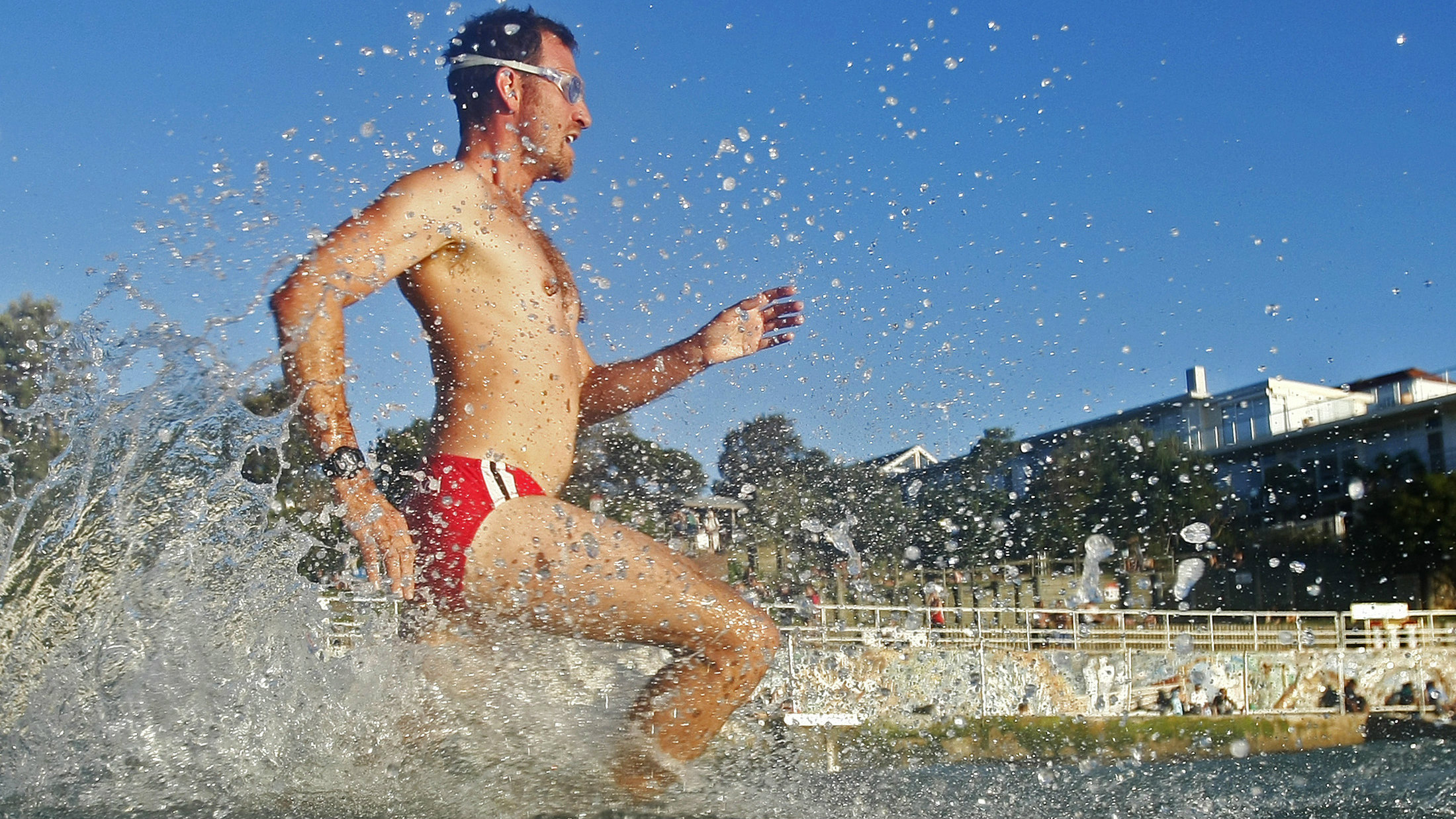 A man runs to the sea for an afternoon swim at Bondi Beach in Sydney December 13, 2012. Australia's iconic Bondi beach receives up to 40,000 visitors on a busy summer day, according to local authorities.