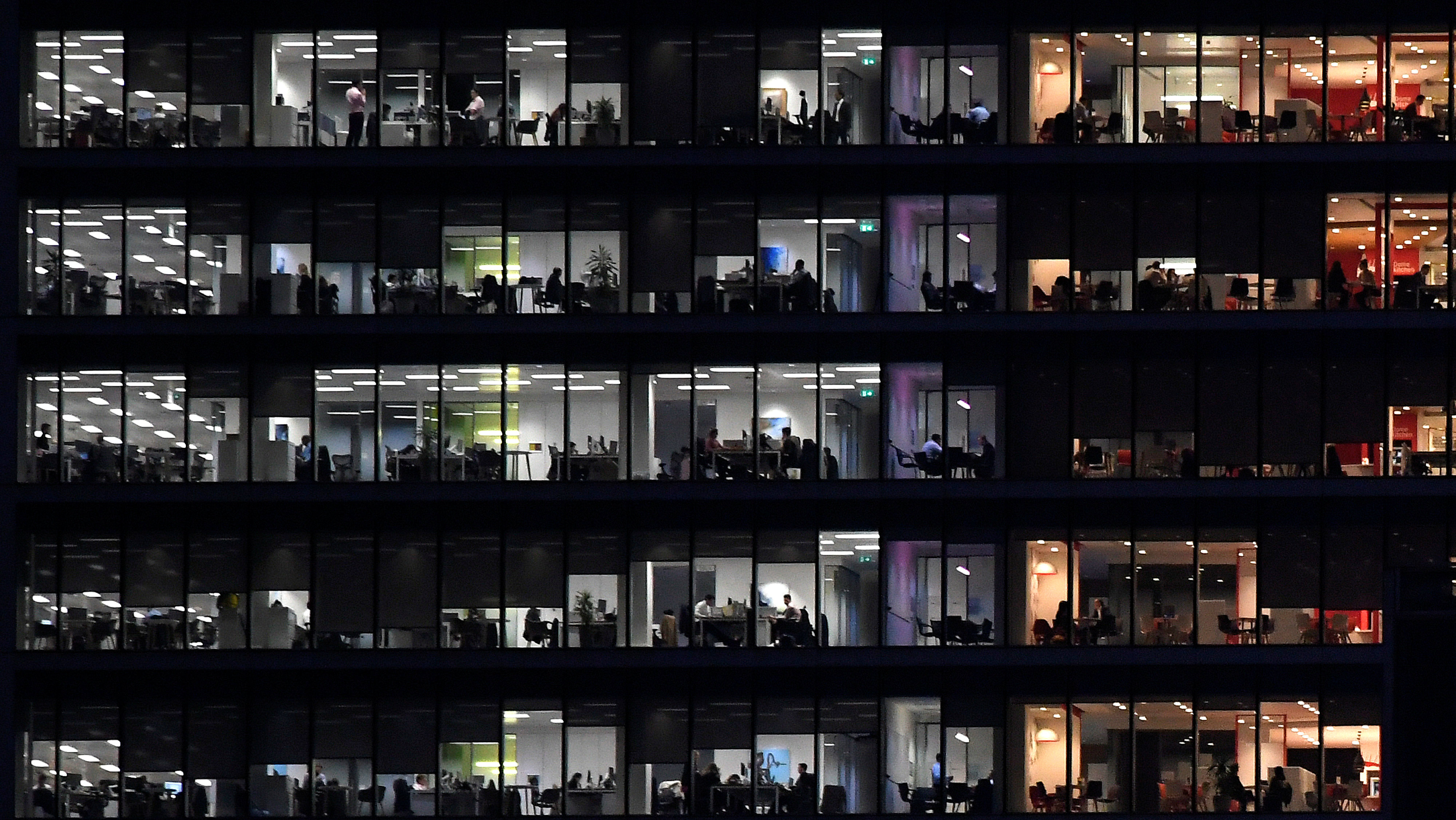 Workers are seen in an office tower in the Canary Wharf financial district at dusk in London, Britain, November 17, 2017. Picture taken November 17, 2017.
