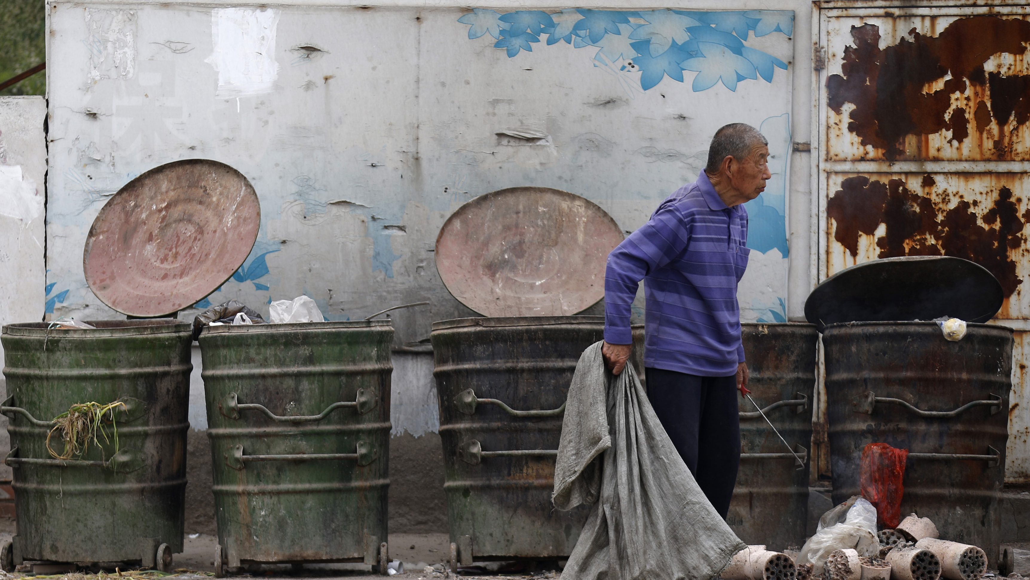 A garbage collector rummages through trash cans to find recyclable garbage at a residential area for migrant workers in Beijing May 7, 2013. For two decades, Chinese local governments have been able to ignore the problem of housing migrants, thanks to the makeshift villages and other arrangements that accommodate about 40 percent of migrants.China has pledged to double household incomes over the coming decade in a bid to close a wealth gap so wide it threatens social stability. Although the proportion of extreme poverty has fallen over recent decades, about 12 percent of the country's 1.3 billion people still live on less than $1.25 per day, according to a 2013 United Nations report. Picture taken on May 7, 2013. REUTERS/Kim Kyung-Hoon (CHINA - Tags: BUSINESS SOCIETY WEALTH) - GM1E99513CW01