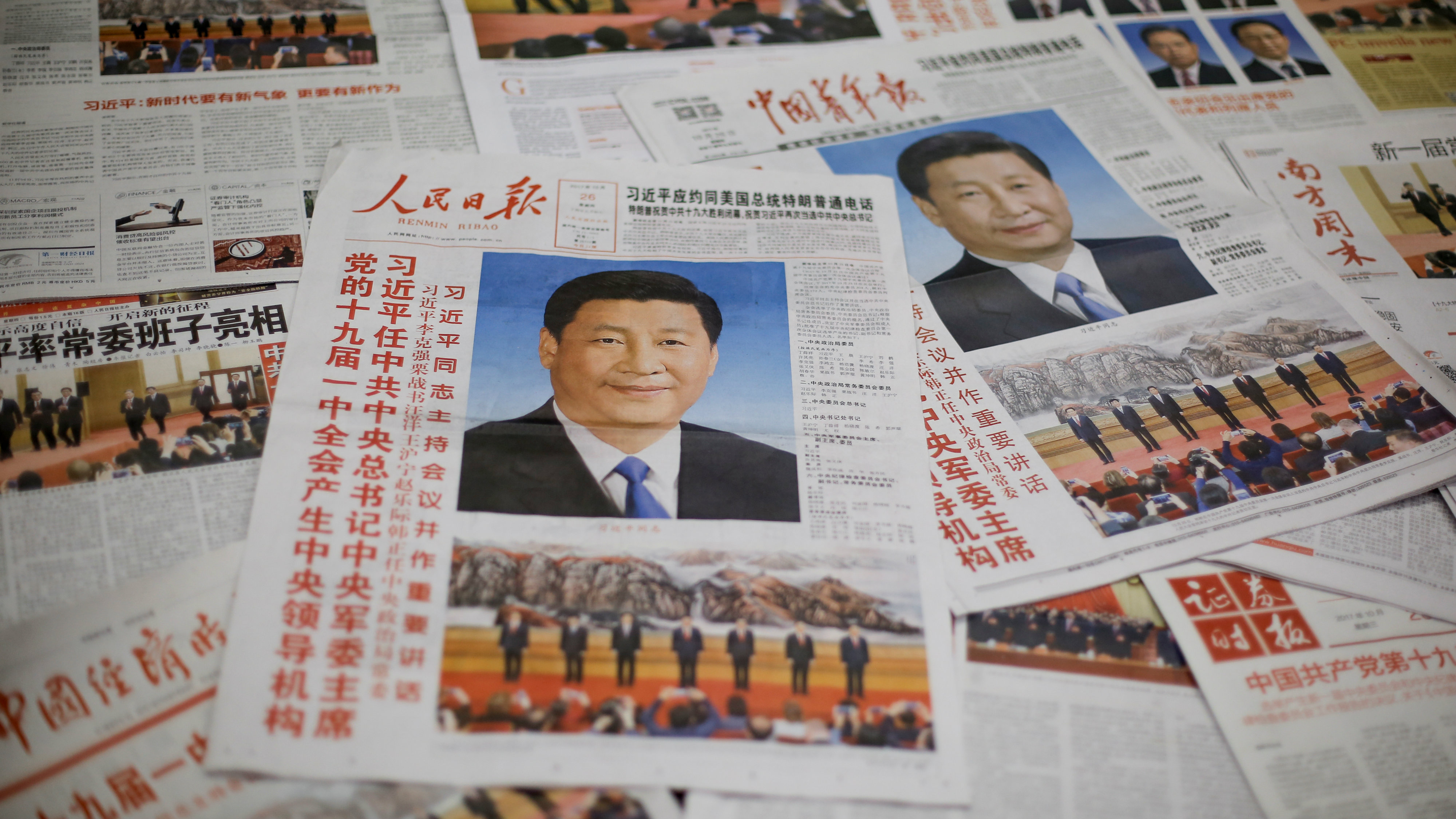The front page of the Communist Party's flagship newspaper the People's Daily (C) and other newspapers are seen one day after the unveiling of the new Politburo Standing Committee in Beijing
