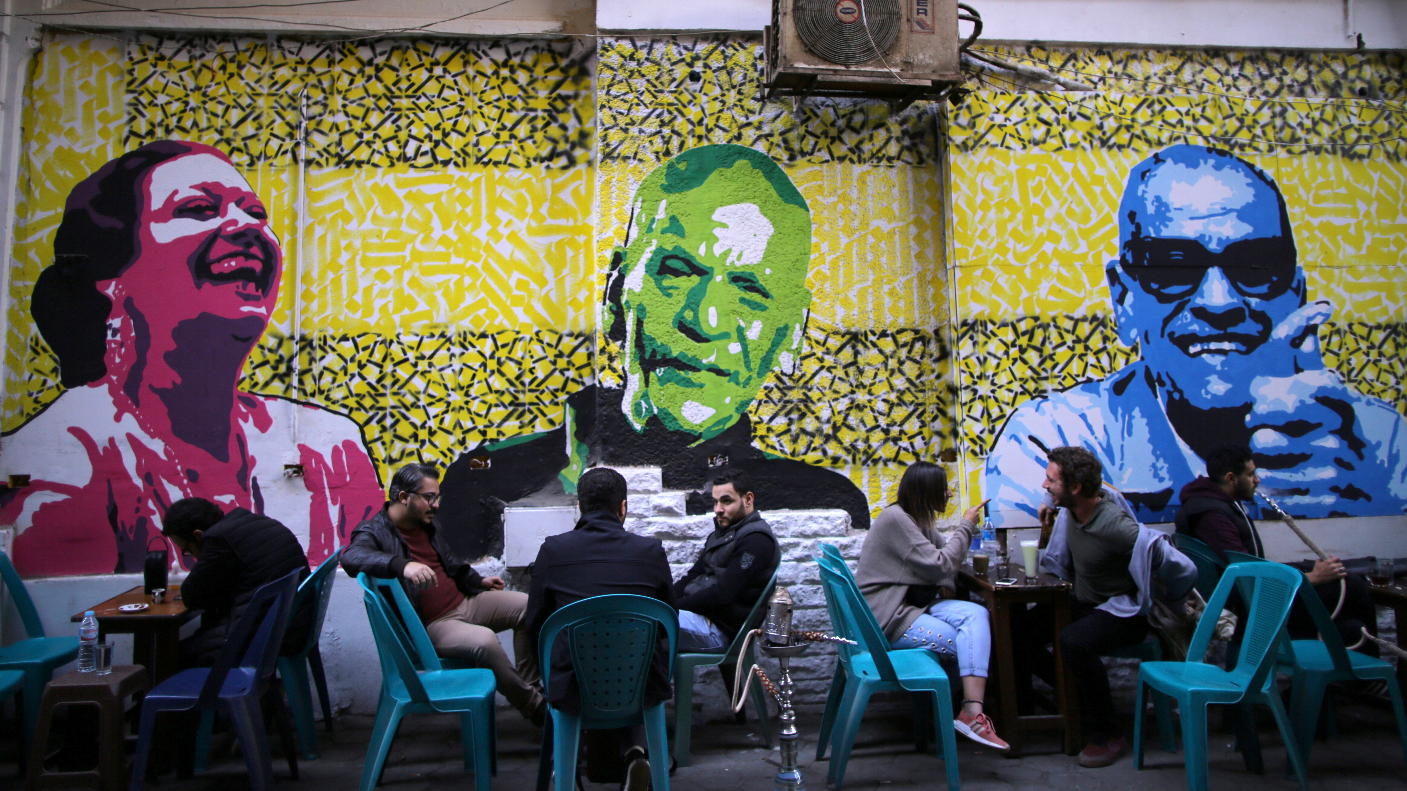 Egyptians sit at a street coffee shop around murals of Egyptian characters and symbols downtown in the capital of Cairo, Egypt January 16, 2018. REUTERS/Amr Abdallah Dalsh NO RESALES. NO ARCHIVES - RC1D720314B0