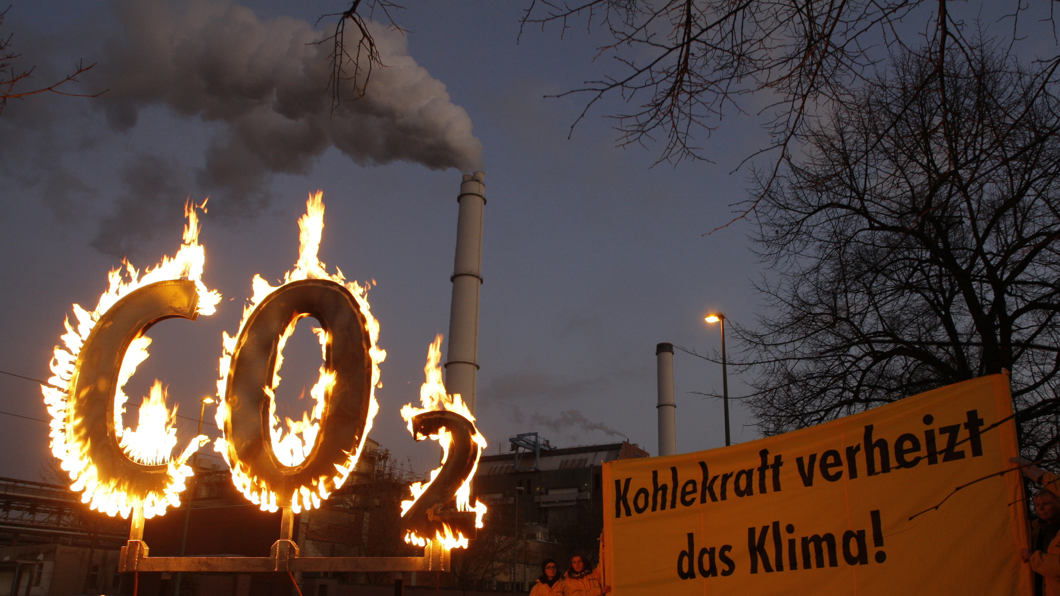 German activists of the environmental organisation Greenpeace illuminate the letters CO2 in front of the Klingenberg coal-fired power plant in Berlin November 13, 2008. The text on the banner reads: 'Coal energy burns the climate.'   REUTERS/Johannes Eisele (GERMANY) - BM2E4BD1CO501