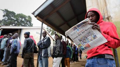 A Kenyan voter (R) reads a local newspaper as other voters queue to cast their votes at a polling station in the Kibera slum, Nairobi, Kenya, 08 August 2017. Kenyans are casting their votes in the general elections, with President Kenyatta being challenged by the popular opposition leader Raila Odinga. During the final week of campaigning, a top election official was murdered amid claims of vote-rigging and President Kenyatta called for calm as fears of post-election violence arose.