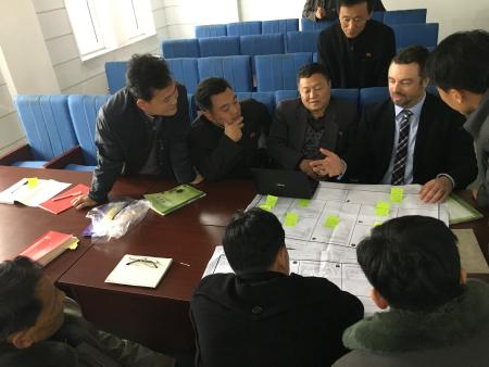Ian Collins explains the business model canvas to a huddle of North Korean seminar participants.