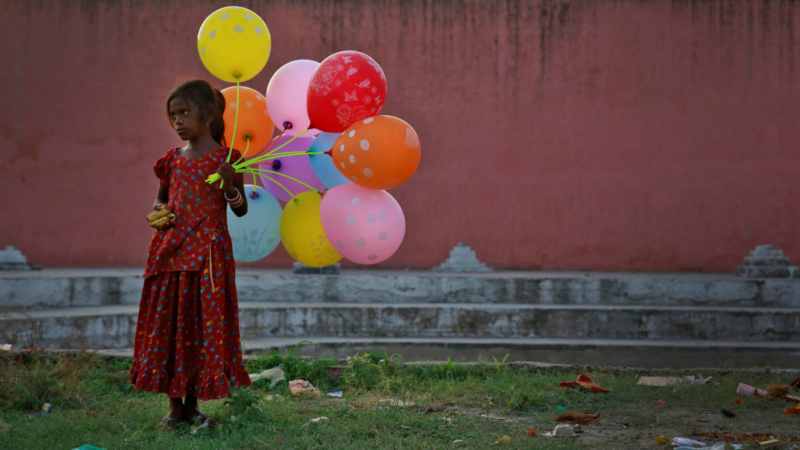 A young girl sells balloons by the Yamuna River on the last day of the ten-day-long Ganesh Chaturthi festival in Delhi, India, September 15, 2016.