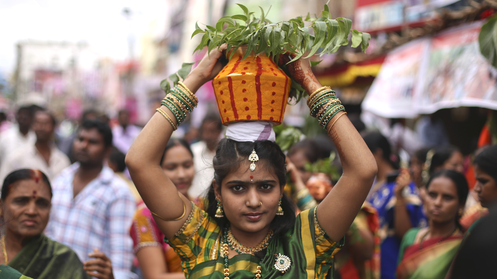 An Indian Hindu woman carries a decorated pot filled with cooked rice as an offering for Hindu goddess Kali during Bonalu festival in Hyderabad, India, Sunday, July 31, 2016. Bonalu is an annual festival celebrated in India's Telangana region.(AP Photo/Mahesh Kumar A.)