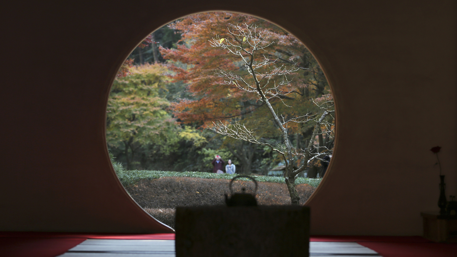 Visitors walk around the ground to view autumn colors they are seen through a circle window of Meigetsuin Temple in Kamakura, near Tokyo, Saturday, Dec. 3, 2016. (AP Photo/Koji Sasahara)