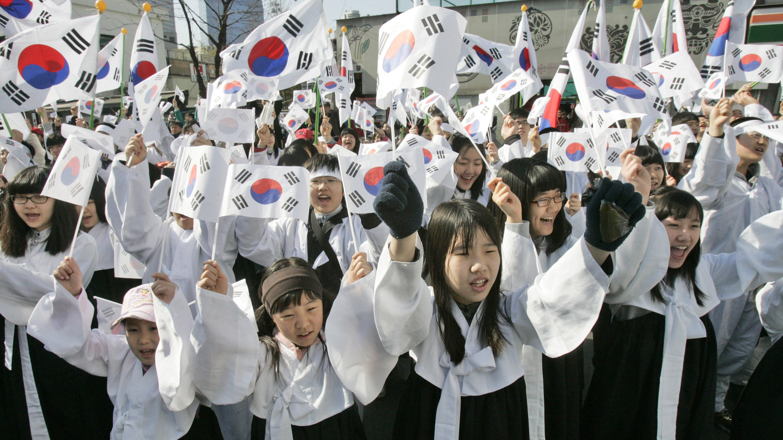 South Korean students wearing traditional Korean costumes shout as they wave their naational flags during a ceremony to celebrate the March First Independence Movement Day, the anniversary of the 1919 uprising against Japanese colonial rule, in Seoul, South Korea, Sunday, March 1, 2009. (AP Photo/Ahn Young-joon)