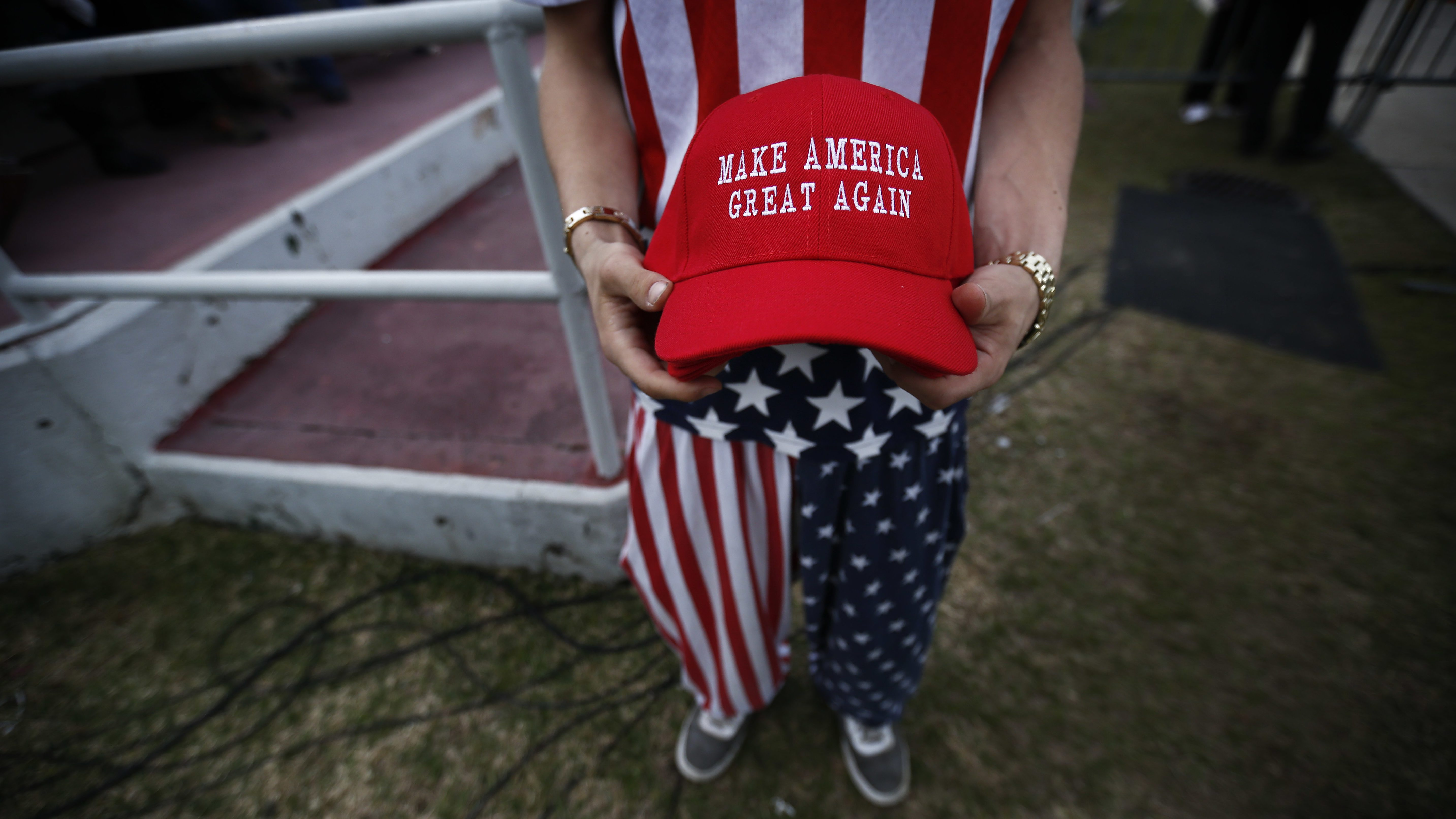 """A man dressed in American flag clothes holds """"Make America Great Again"""" hats"""