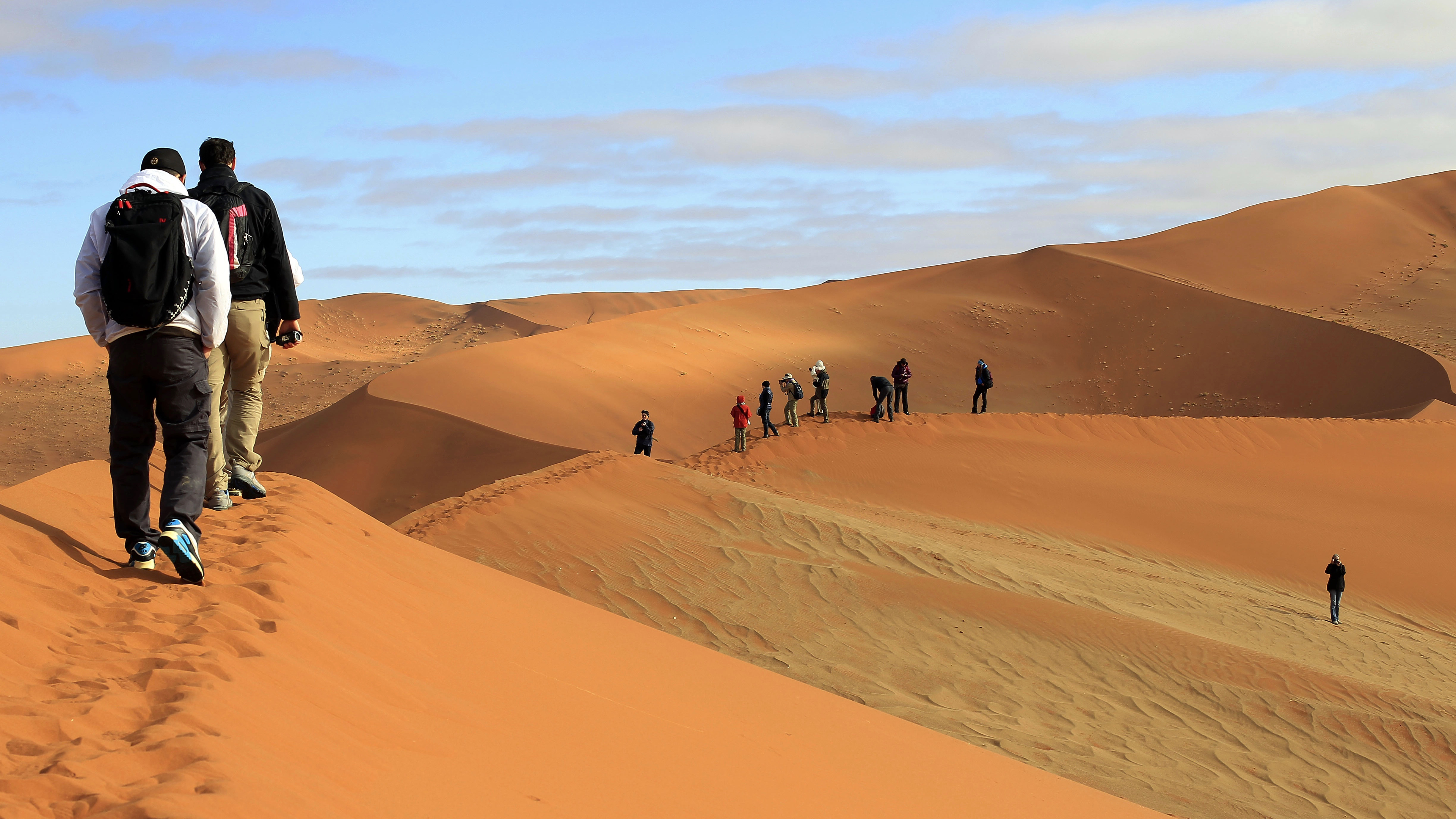 In this photo taken Sunday  Aug. 11 2013, tourists walk the dunes of Sossuslvei in Southern Namibia. Desert tourism attracts tens of thousands of tourists a year in this Southern African country of just over two millions. Further North,  An estimated 778,000 Namibians, which equates to a third of the country's population , are either severely or moderately food insecure due to the worst drought in years. (AP Photo/Jerome Delay)