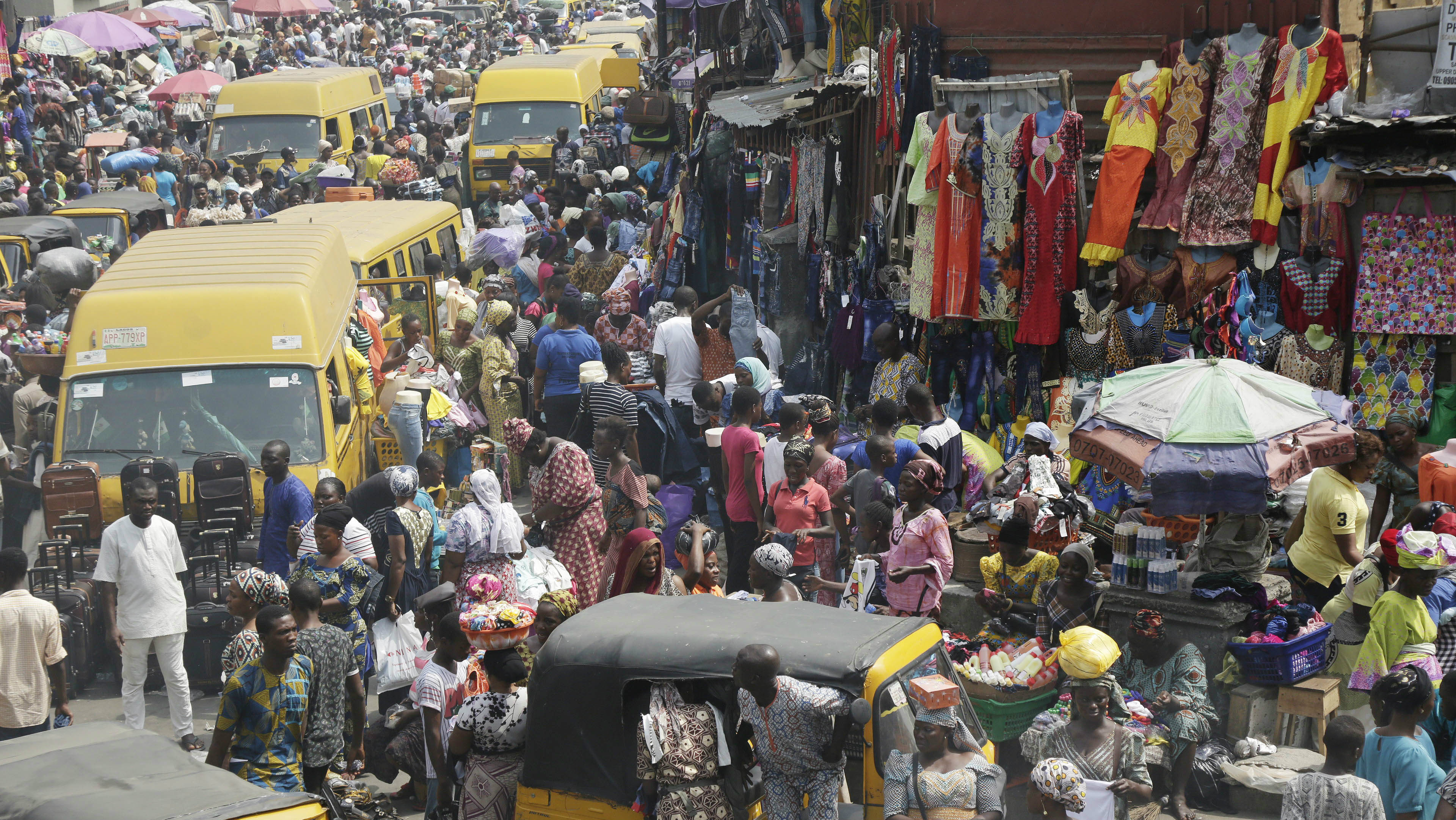 Pedestrians shop at Balogun market ahead of Christmas celebrations, in Lagos, Nigeria, Friday, Dec. 23, 2016.
