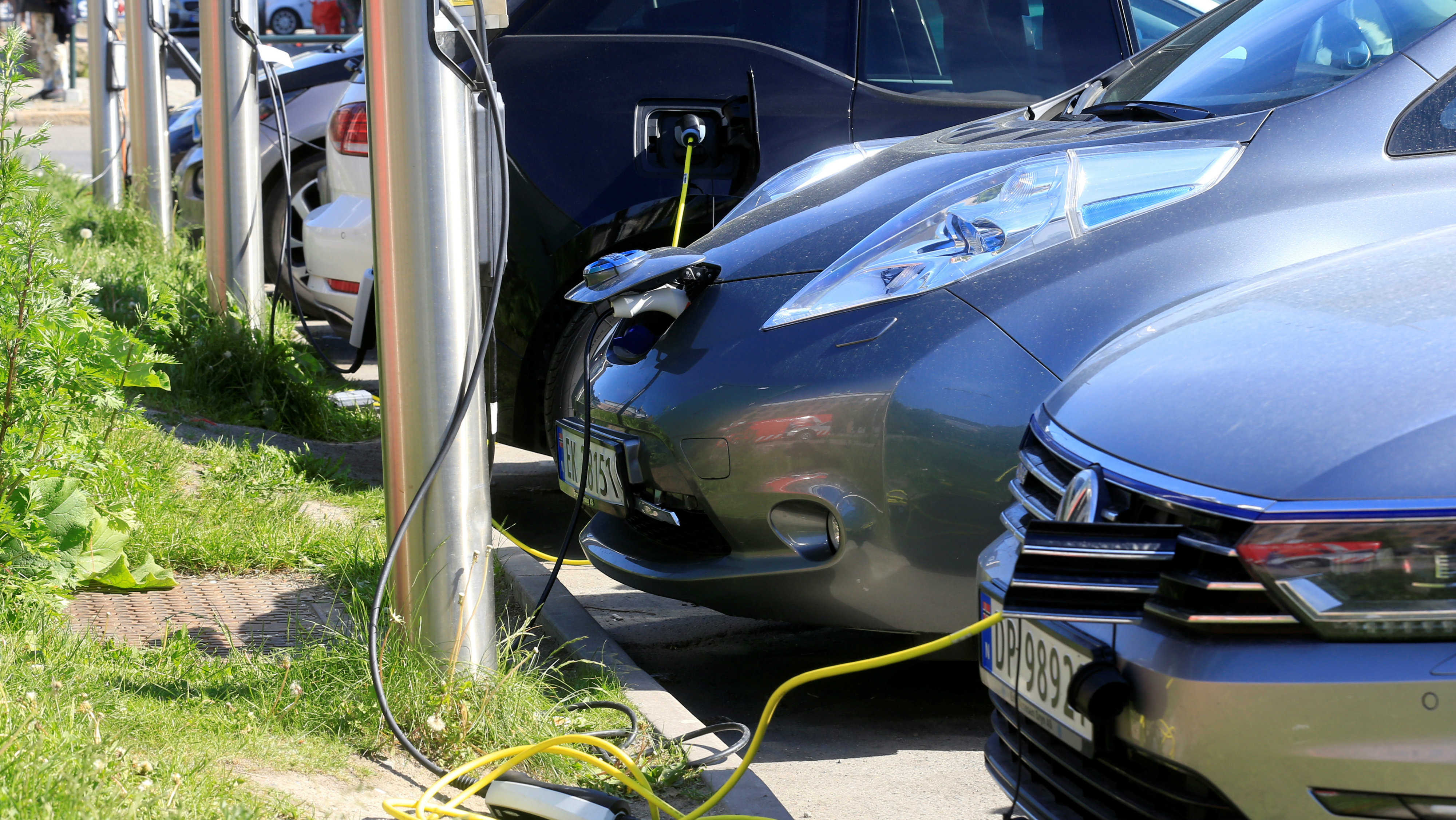 Electric cars are charged at a parking lot in Oslo, Norway.