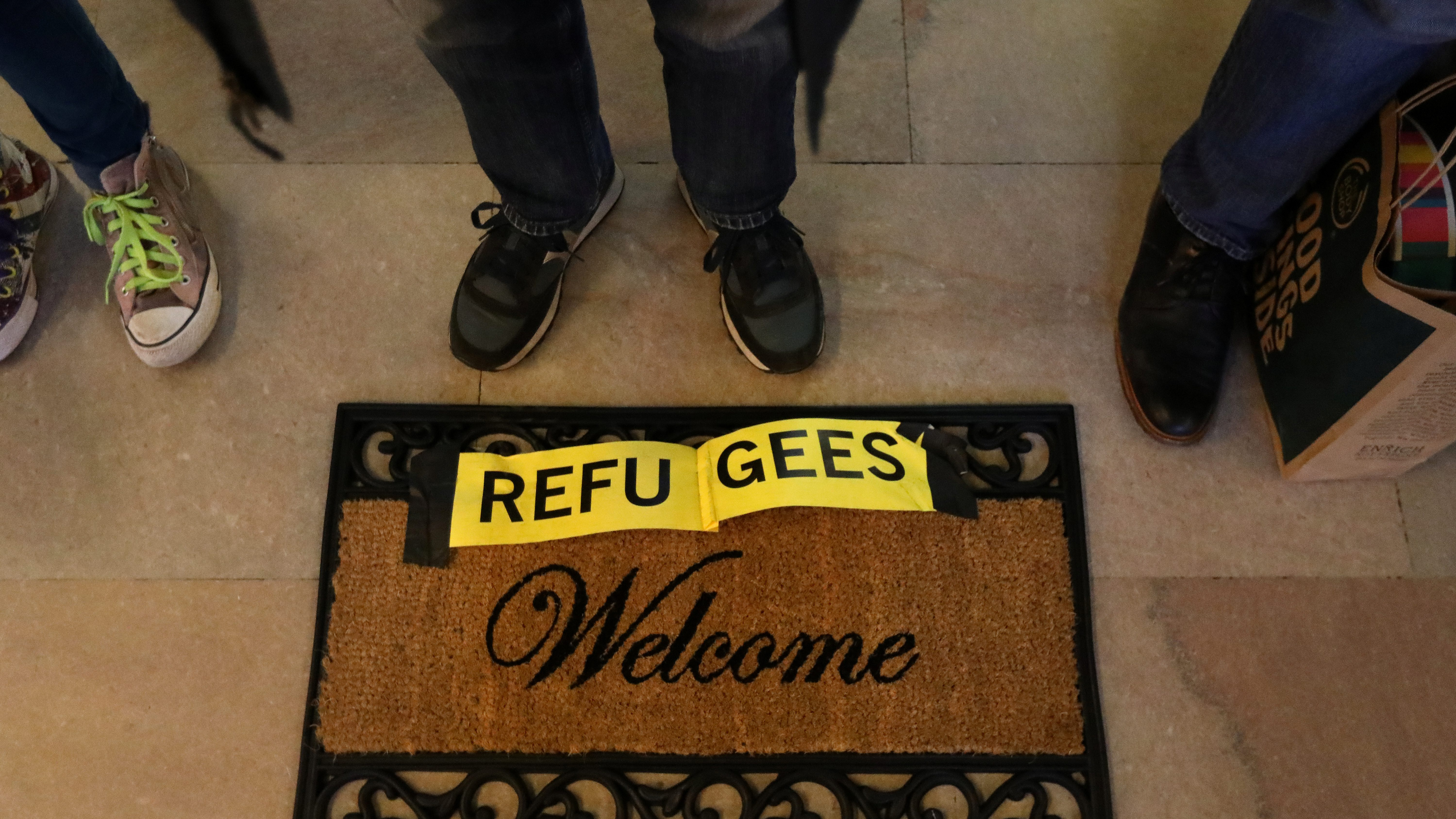 """People stand by a """"Refugees Welcome"""" mat"""
