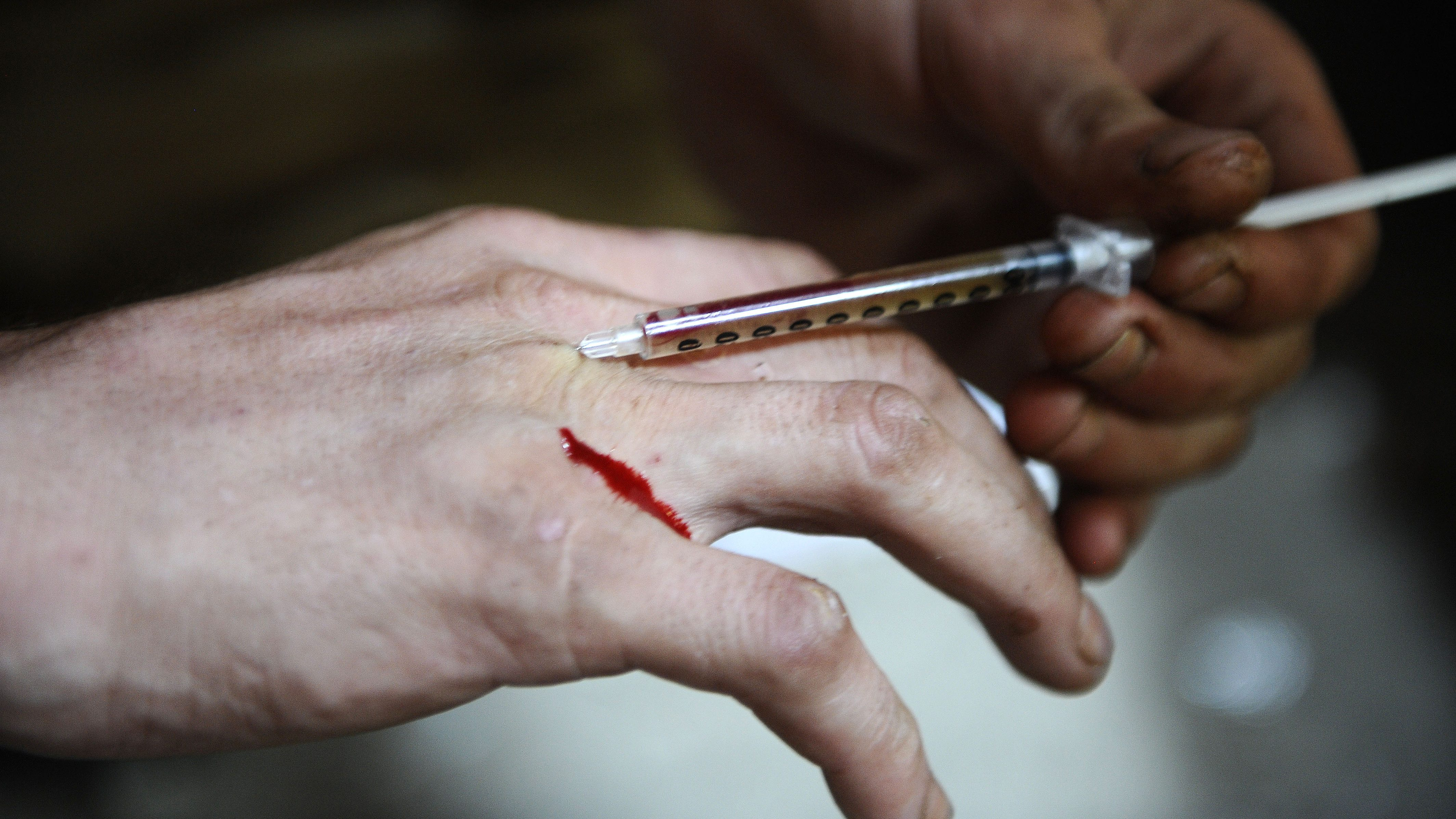 A man injects heroin into a vein in his hand at an abandoned house in Ljubljana