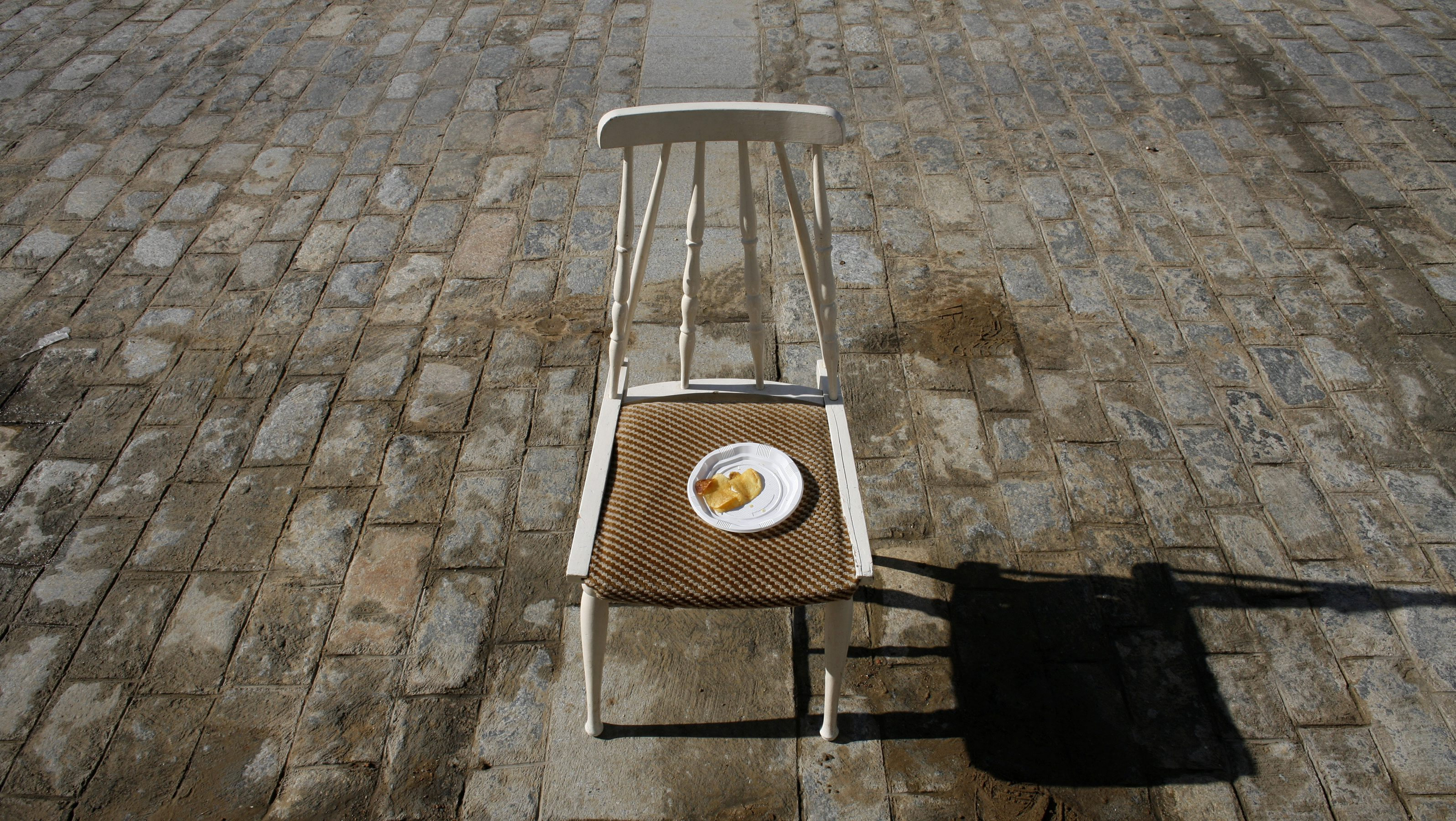 A plate of crisps is seen on a chair in a central street during a festival in Spain.