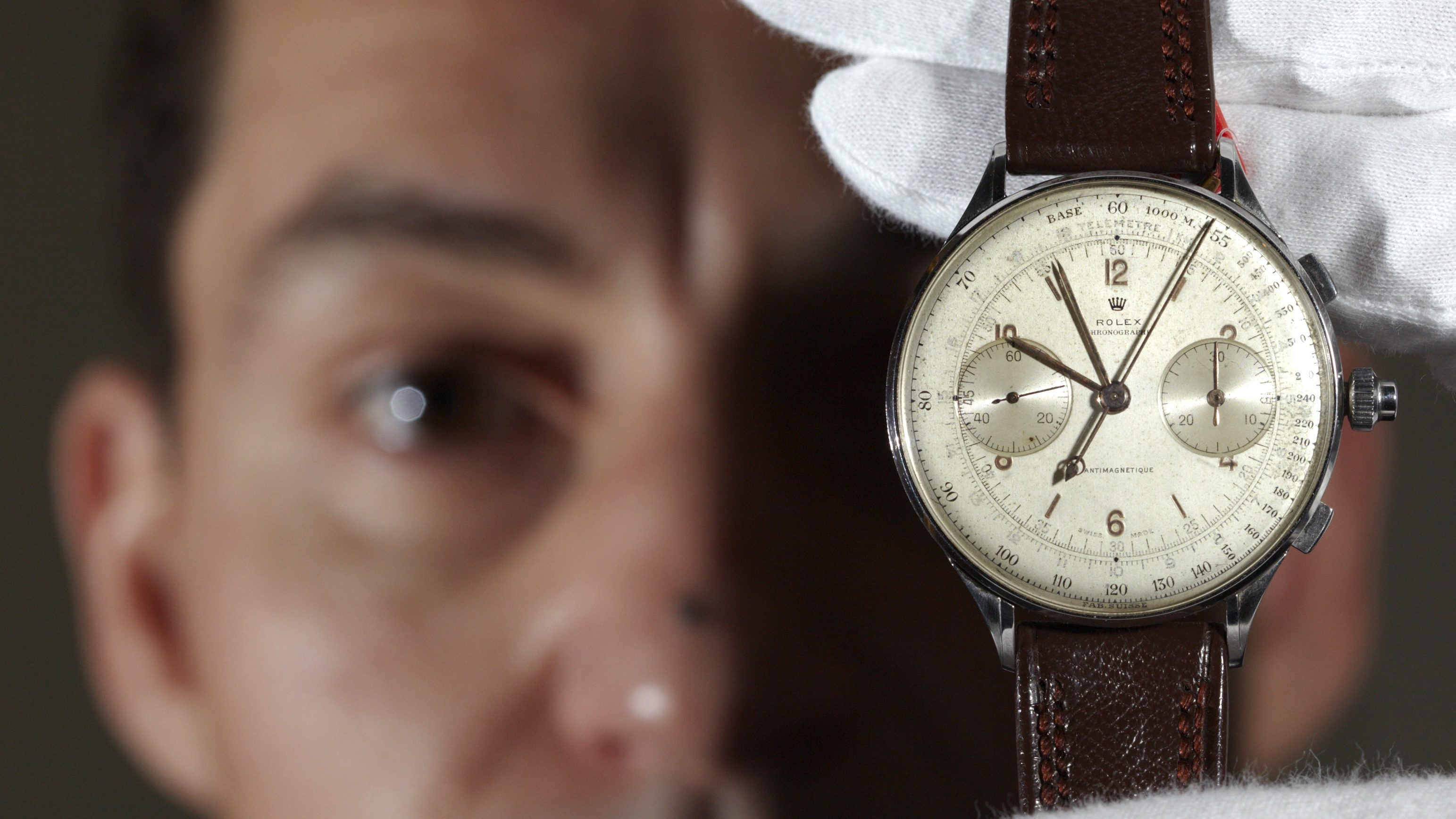 A Christie's member of staff displays a rare oversized stainless steel split second chronograph wristwatch made by Rolex circa 1942 during an auction preview in Geneva